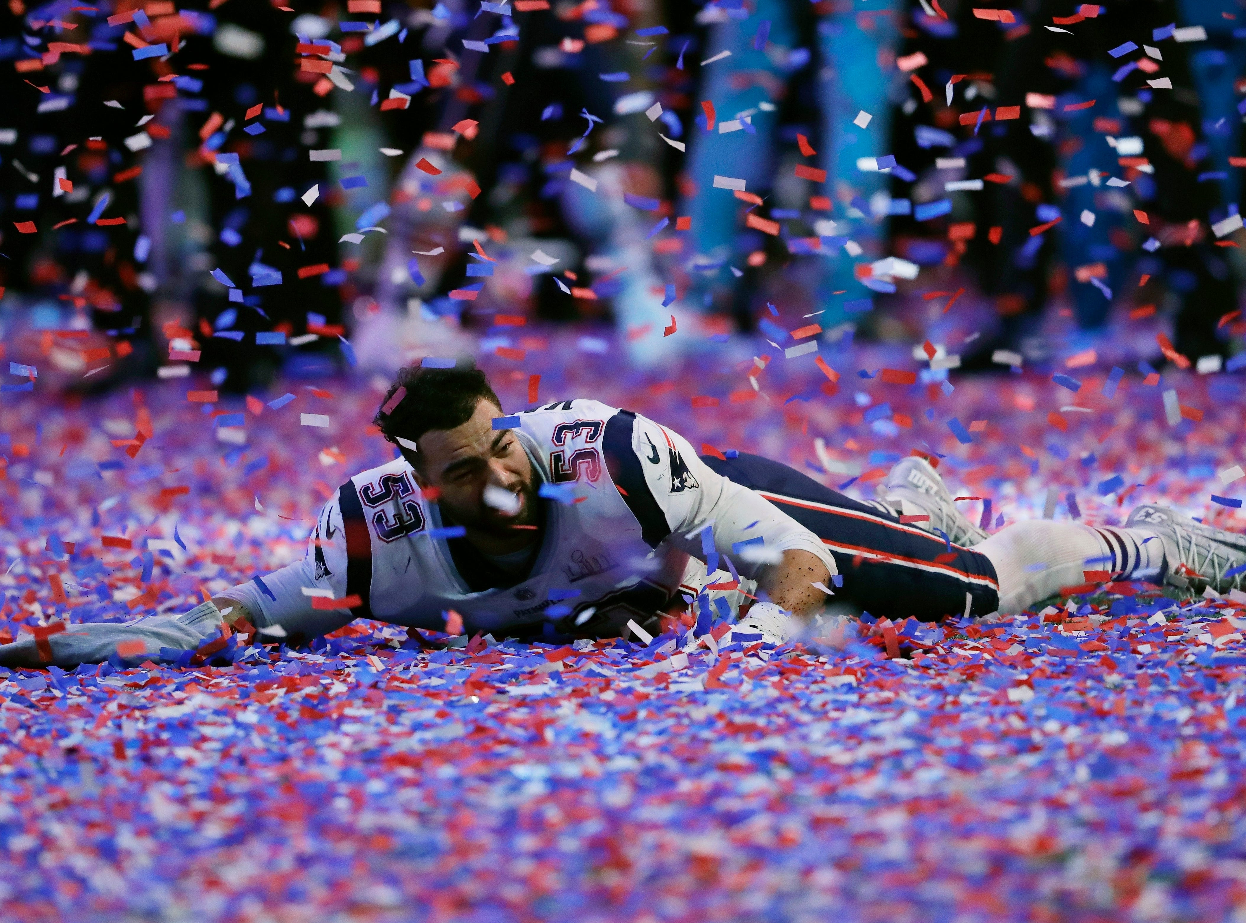 New England Patriots' Kyle Van Noy celebrates in confetti on the turf after the game.