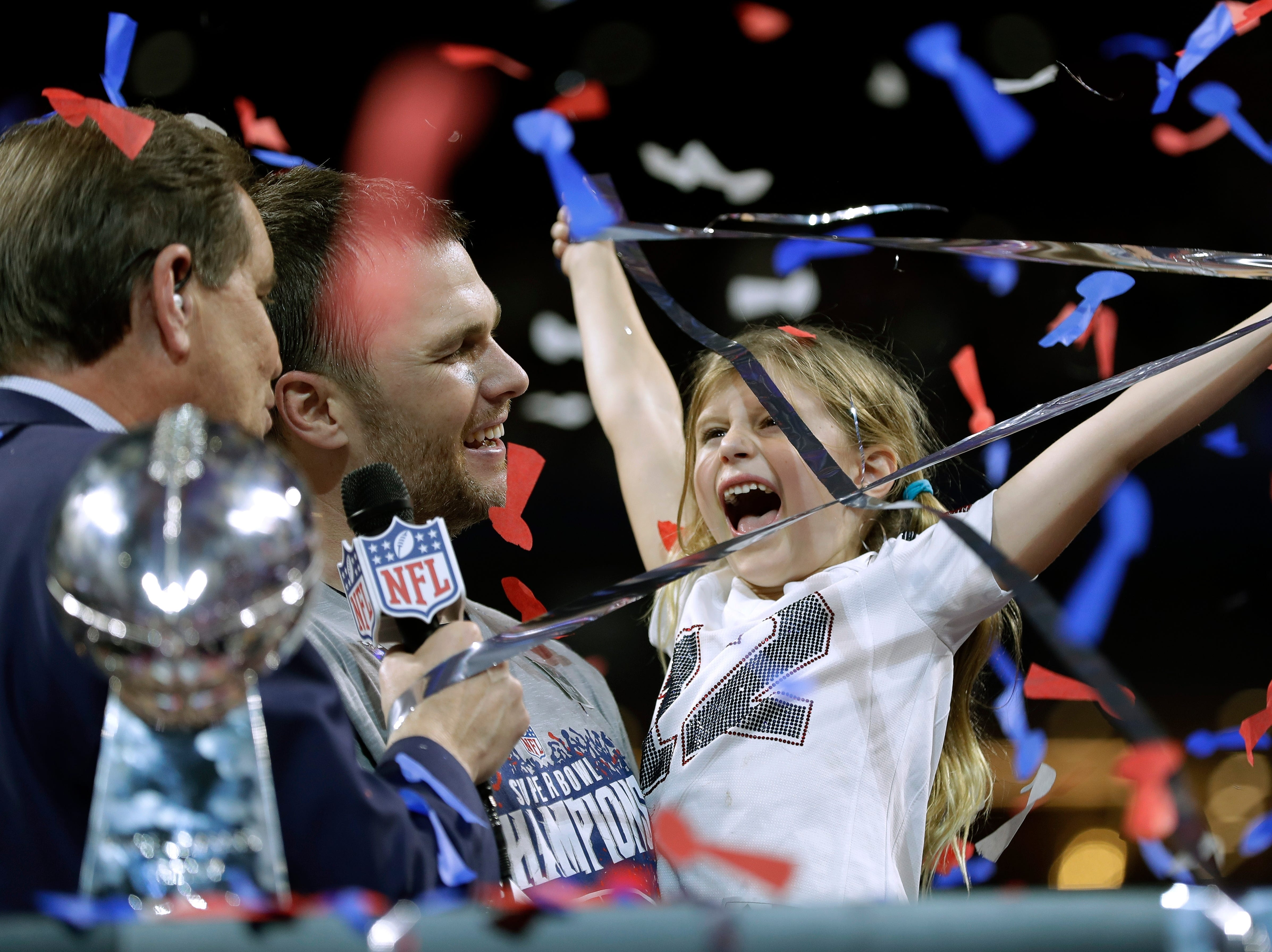 New England Patriots' Tom Brady celebrates with his daughter, Vivian, after the game.