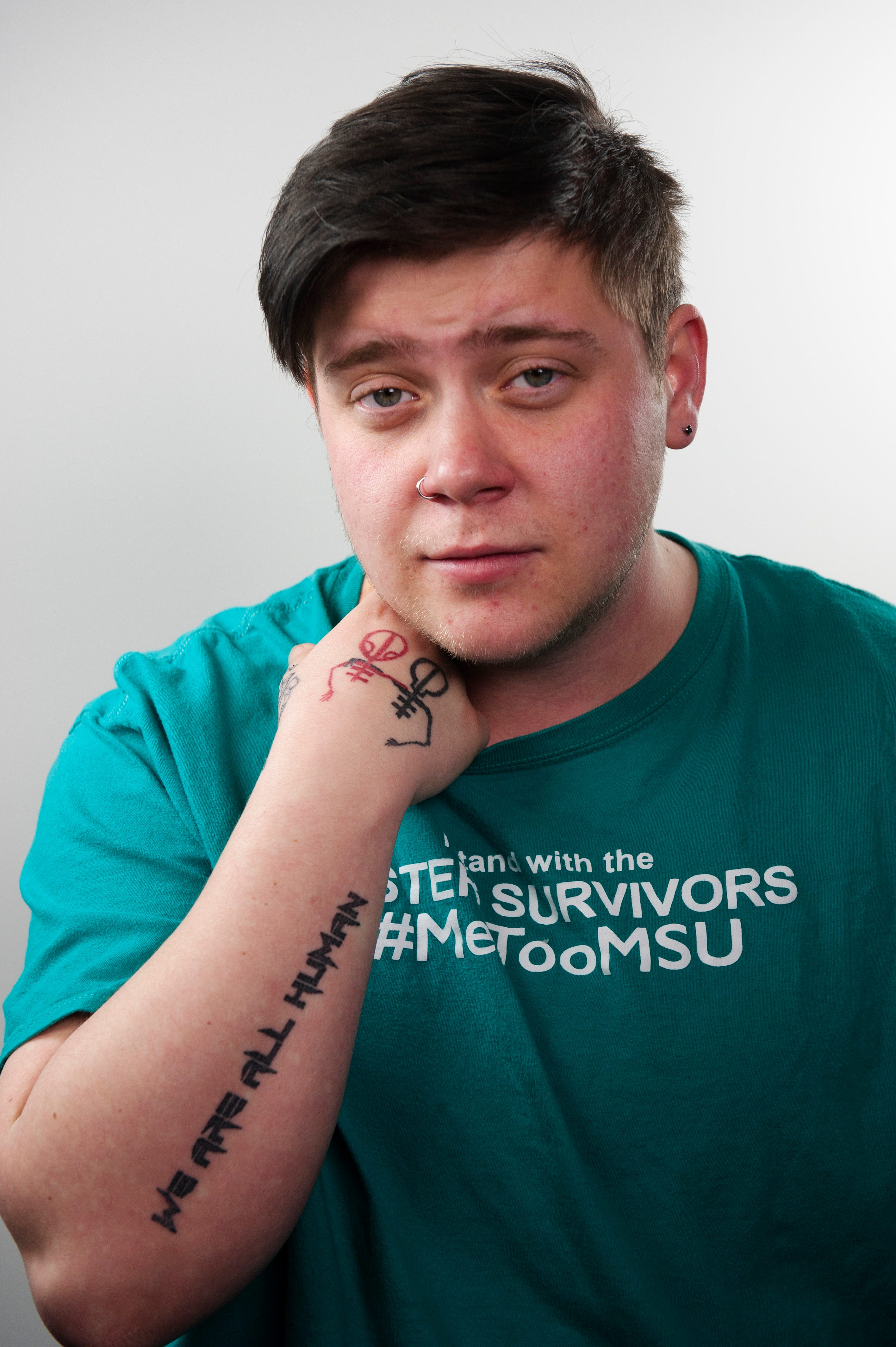"""Zach Ashcraft, 25, of Mason, Michigan shows his """"We are all human"""" tattoo.  Ashcraft was known as Meaghan when as a 10-year-old female gymnast he met and was later abused by Larry Nassar. Ashcraft  is transgender and now identifies as male."""