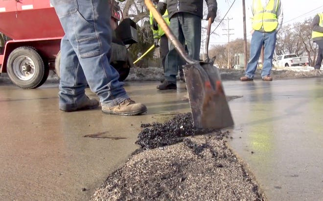 Warren Evans joined one of the county's road patching crews on Merriman Road near Michigan Avenue in the city of Wayne with temperatures rapidly rising and roads deteriorating.