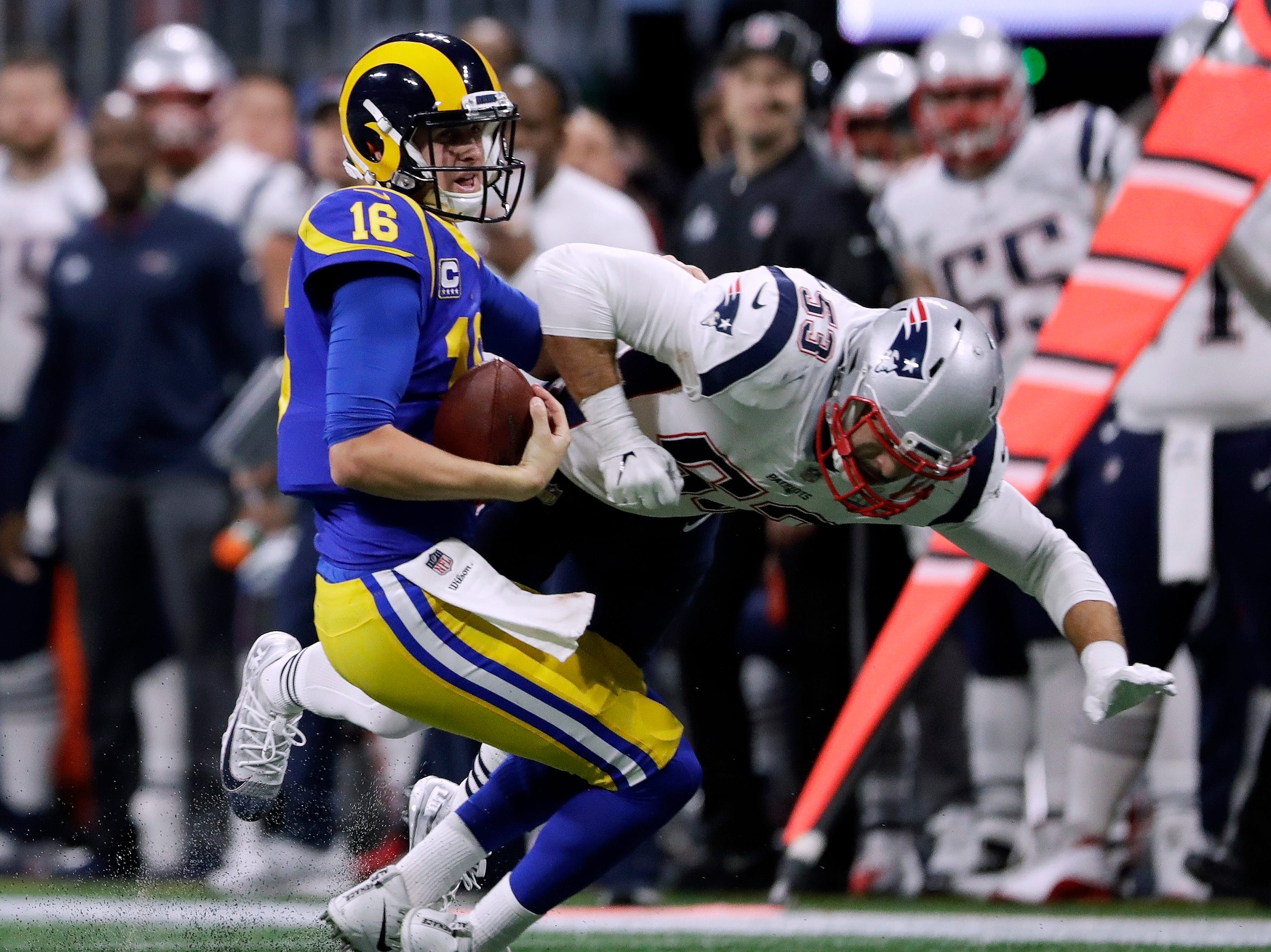 Los Angeles Rams' Jared Goff (16) gets sacked by New England Patriots' Kyle Van Noy (53) during the first half.