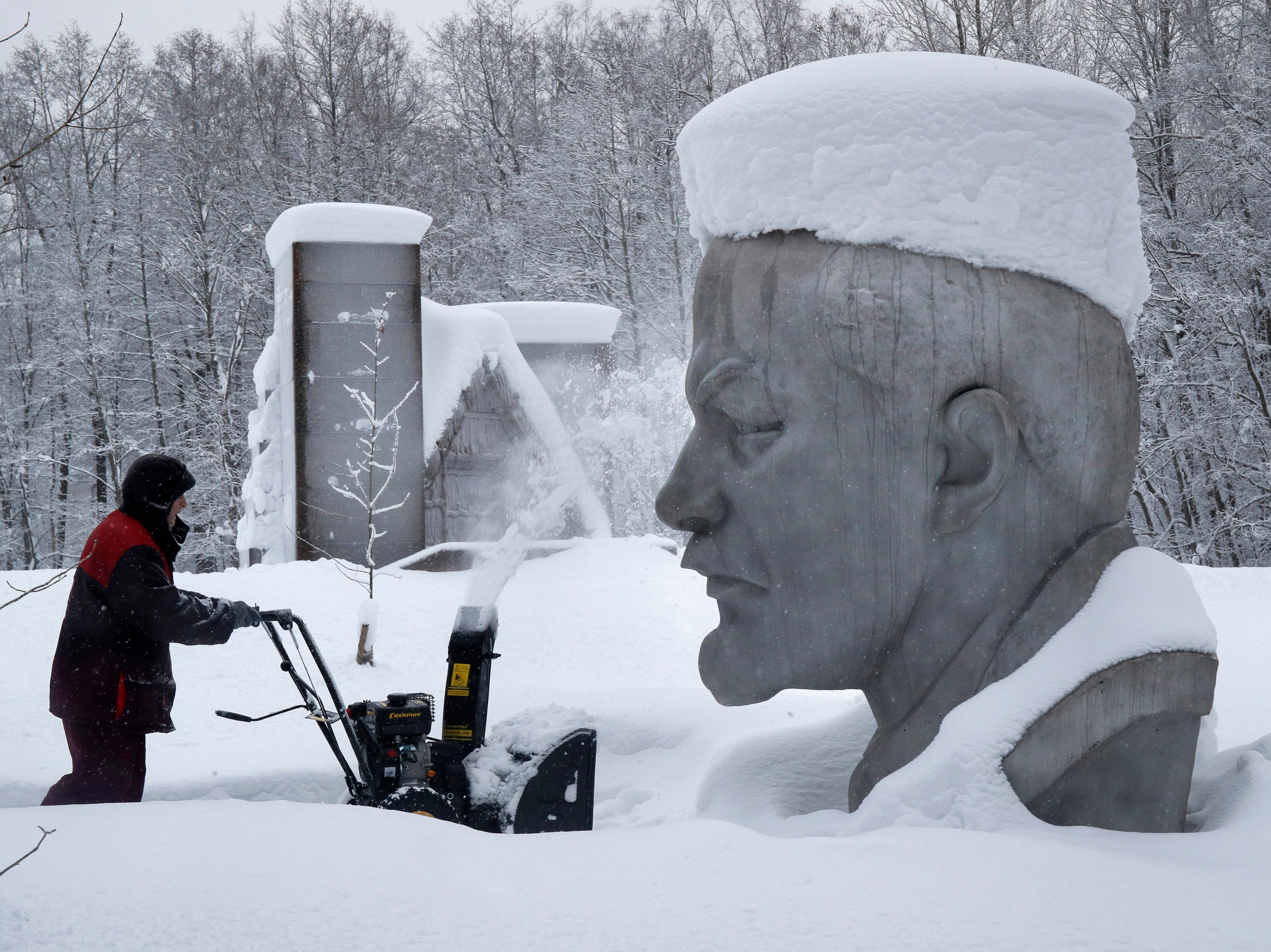 A worker clears snow next to the snow covered statue of Soviet Union founder Vladimir Lenin at the Lenin Hut Museum in a forest near Razliv Lake, outside St. Petersburg, Russia, Monday, Feb. 4, 2019. Another cyclone caused a week of snowfall in St. Petersburg.