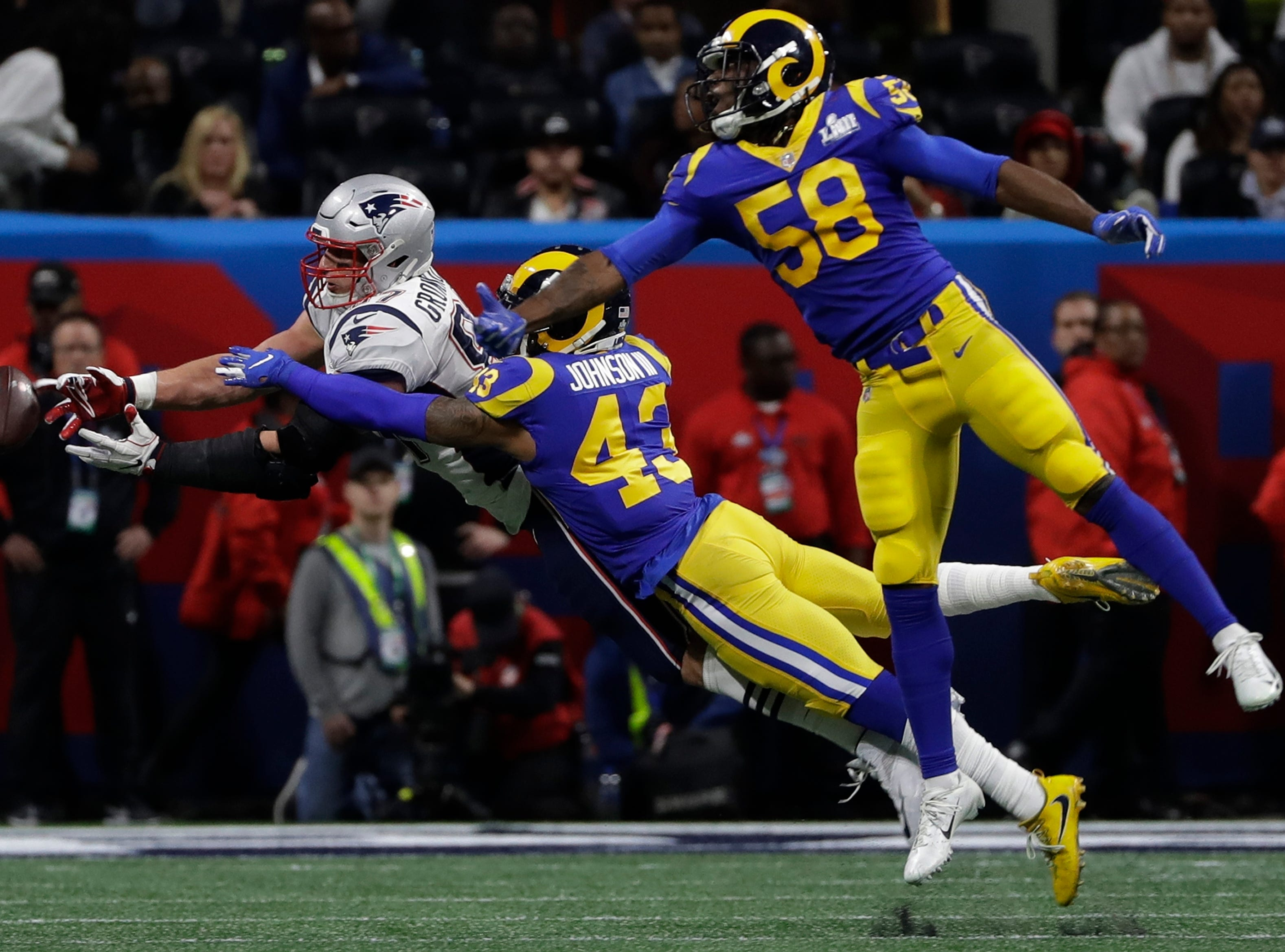 New England Patriots' Rob Gronkowski (87) stretches to catch a pass as Los Angeles Rams' Cory Littleton (58) and John Johnson III (43) defend, during the first half.