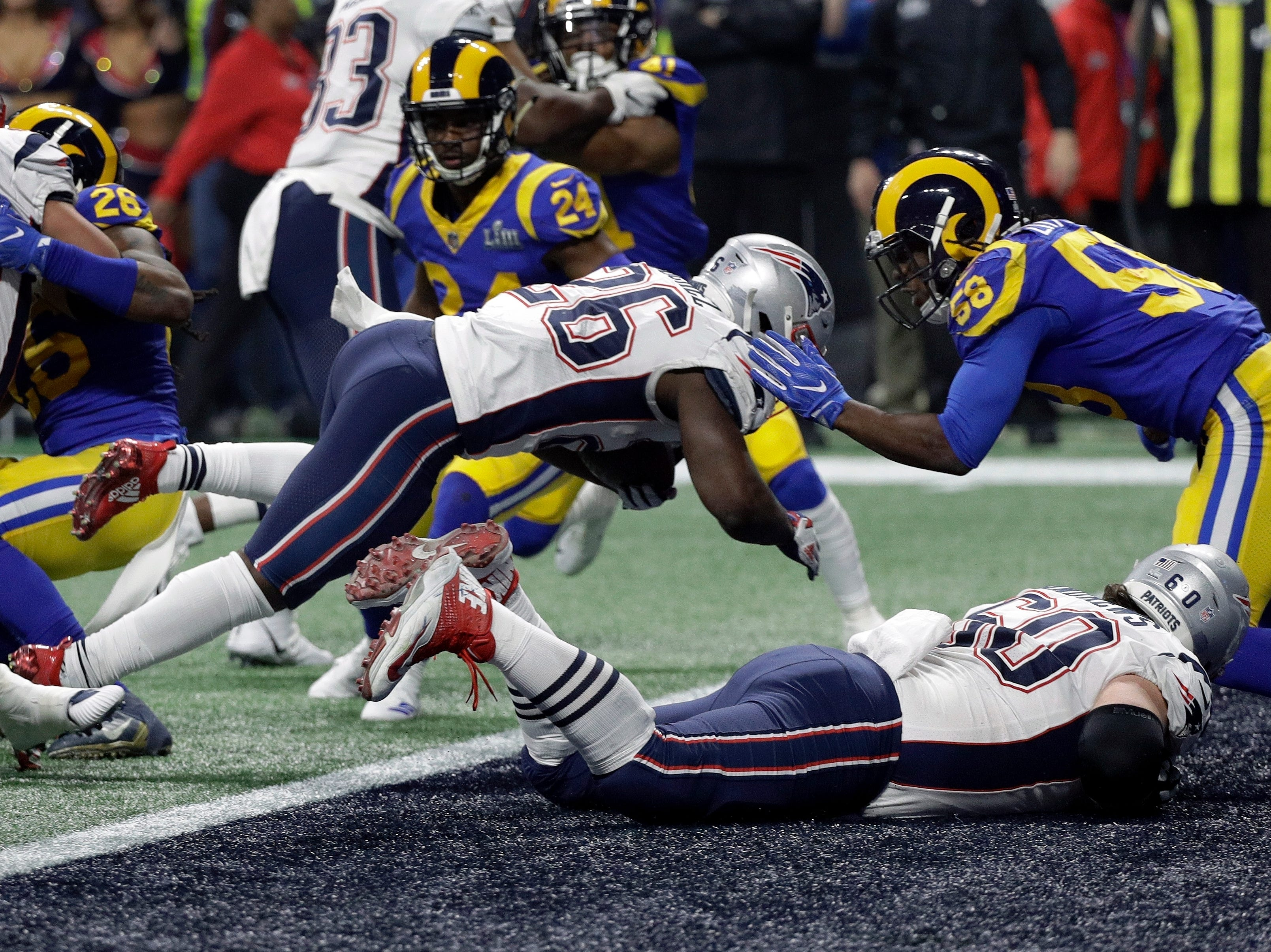 New England Patriots' Sony Michel (26) dives over the goal line for a touchdown in front of Los Angeles Rams' Cory Littleton (58) during the second half.