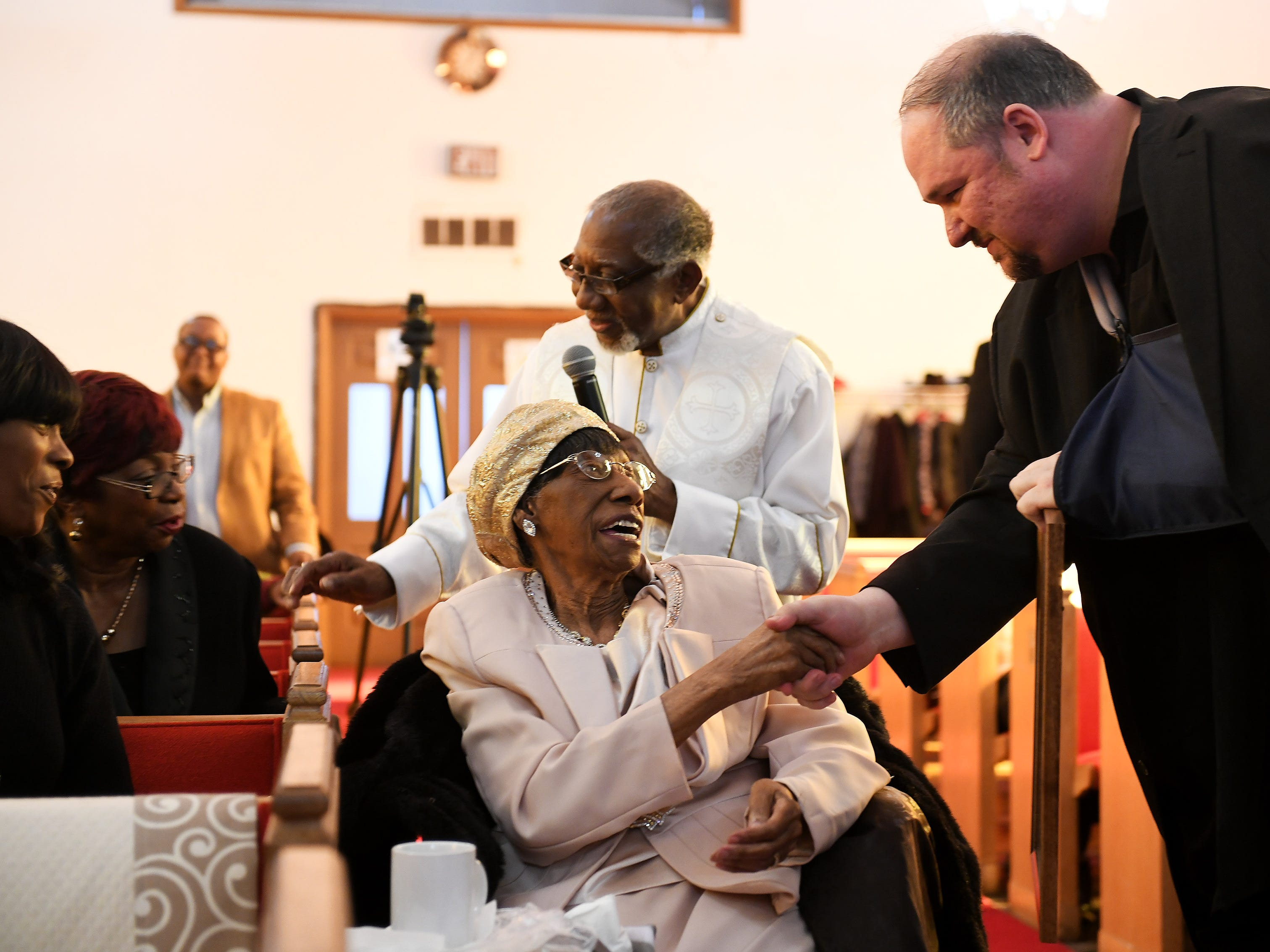 """The Rev. Earnest O. King, Sr., behind """"Mother"""" Lois Holden, introduces Holden's niece, Cerita Cade, second from left, while state Rep. Isaac Robinson, right, shakes hands with Lois Holden after presenting her with a proclamation."""
