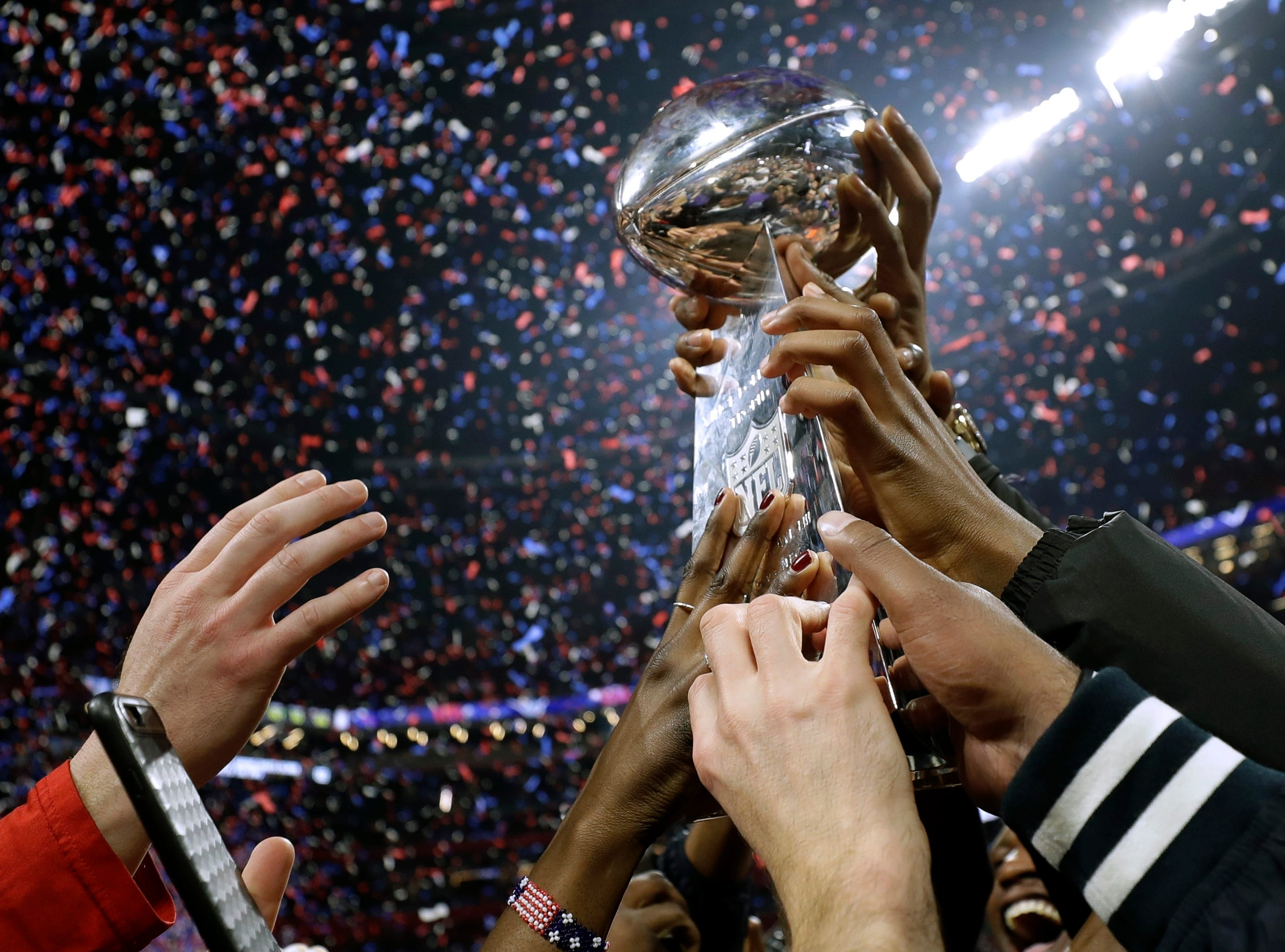 New England Patriots players and family members hold the Lombardi trophy after the game.
