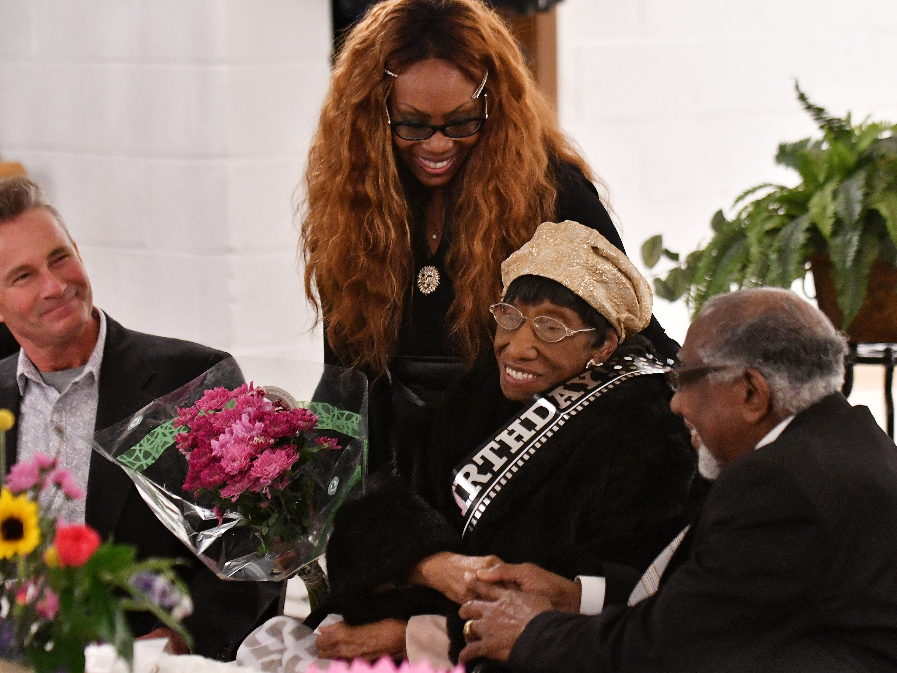 """The Rev. Earnest O. King Sr. right, holds the hand of """"Mother"""" Lois Holden while King's daughter Emeline King presents Holden with flowers, and John Awrey of Brighton, left, who was raised by Holden, smiles."""