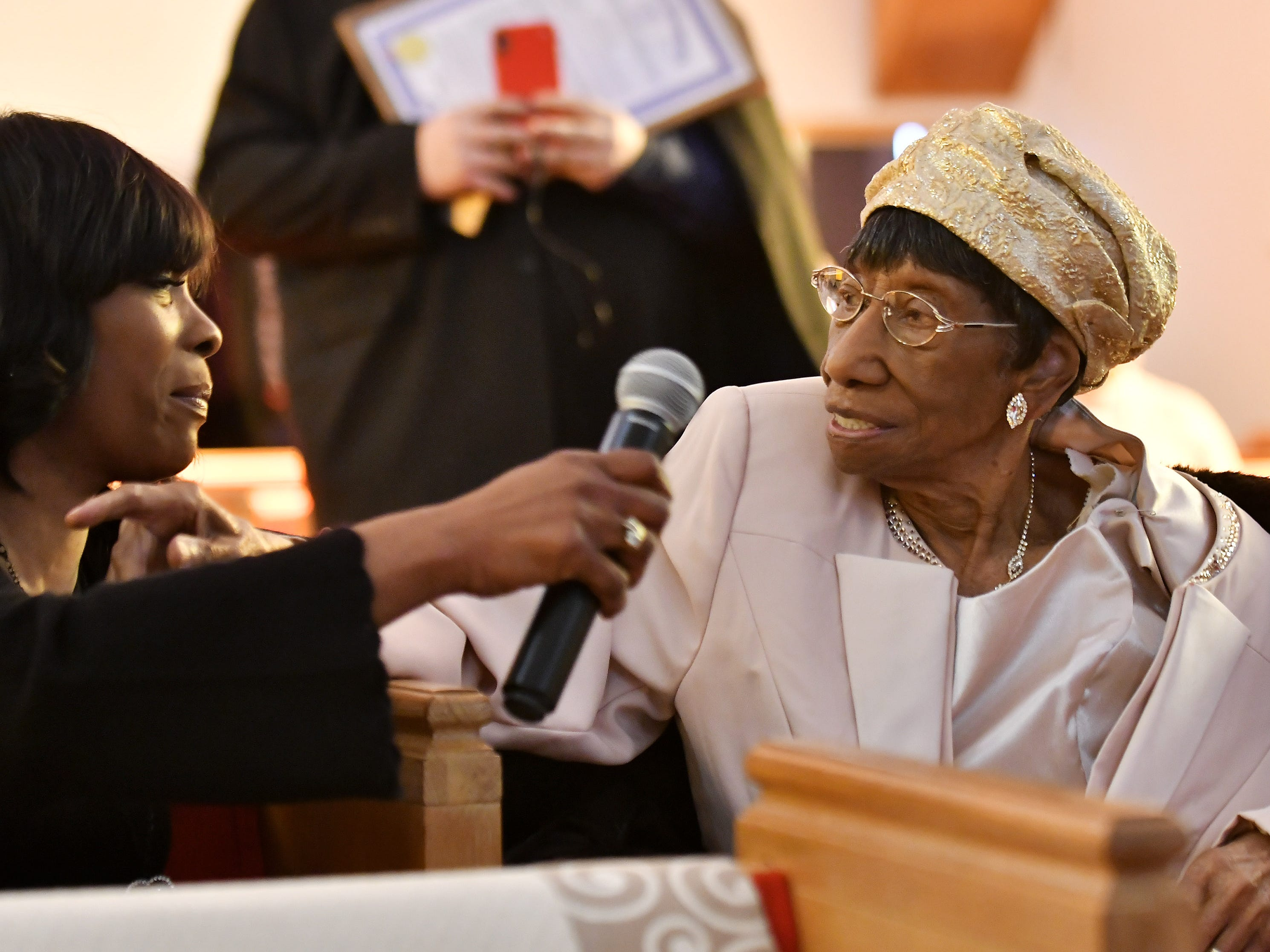 """Michelle Williams reaches a microphone over to her grandmother, """"Mother"""" Lois Holden so she can speak at the end of the service. Michelle also takes care of Lois Holden full time."""