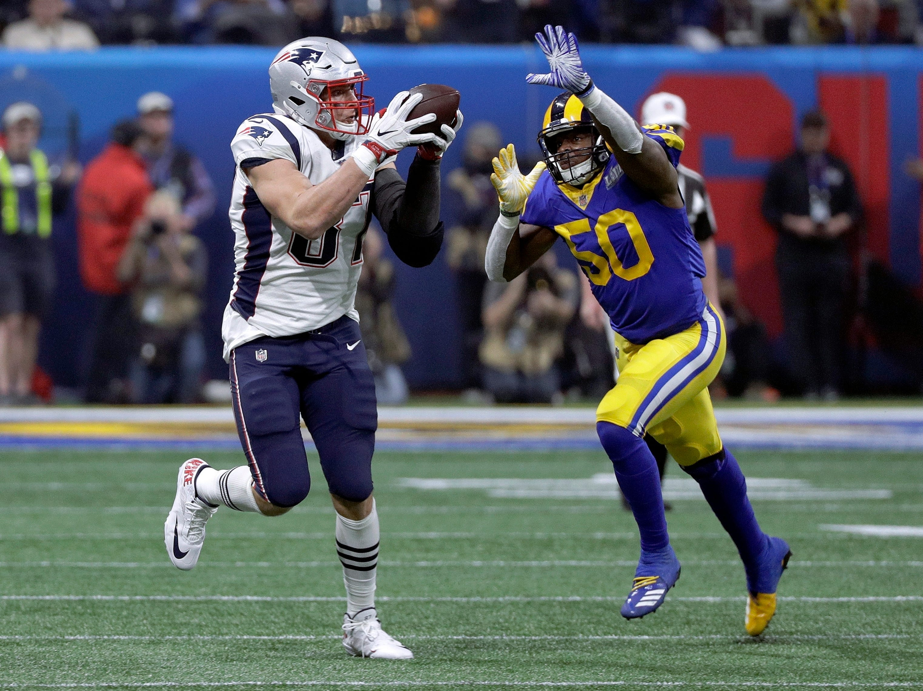 New England Patriots' Rob Gronkowski (87) catches a pass in front of Los Angeles Rams' Samson Ebukam (50) during the second half.