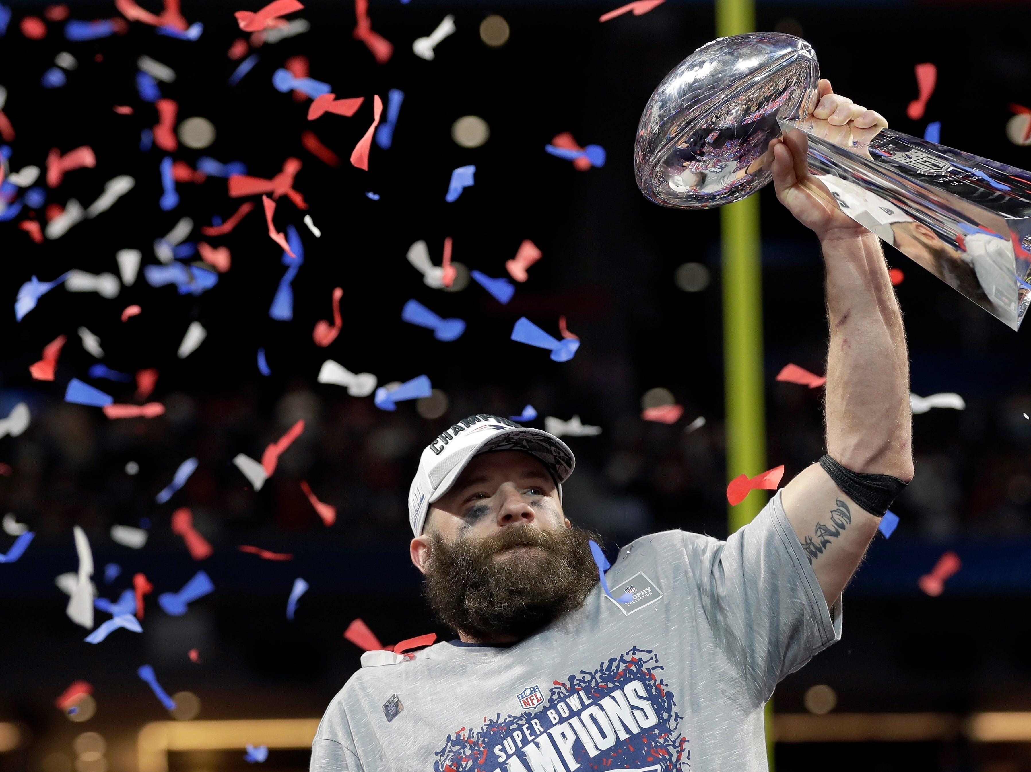New England Patriots' Julian Edelman holds the Lombardi trophy after the game.
