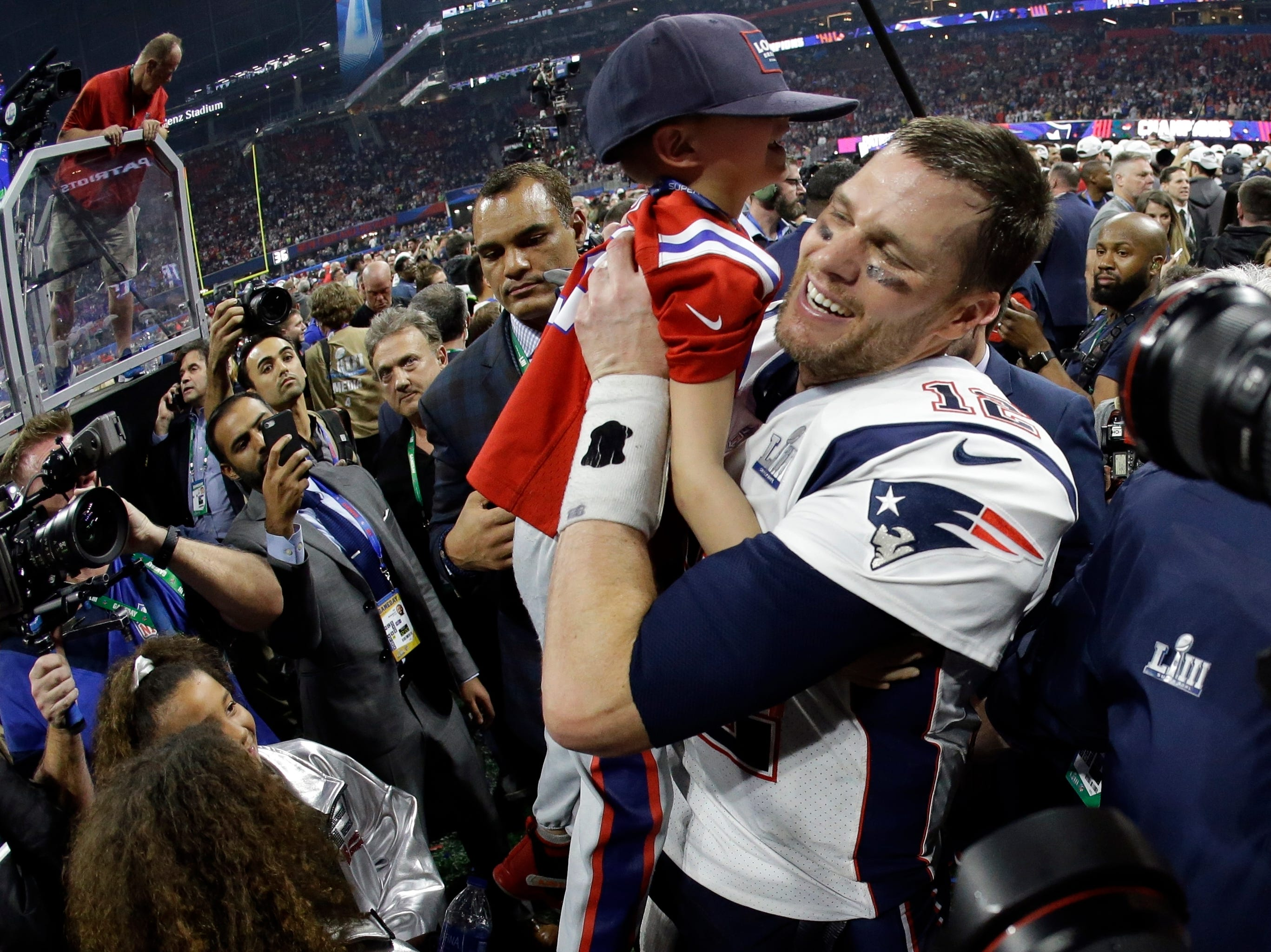 New England Patriots' Tom Brady lifts his son, Ben, after the game.
