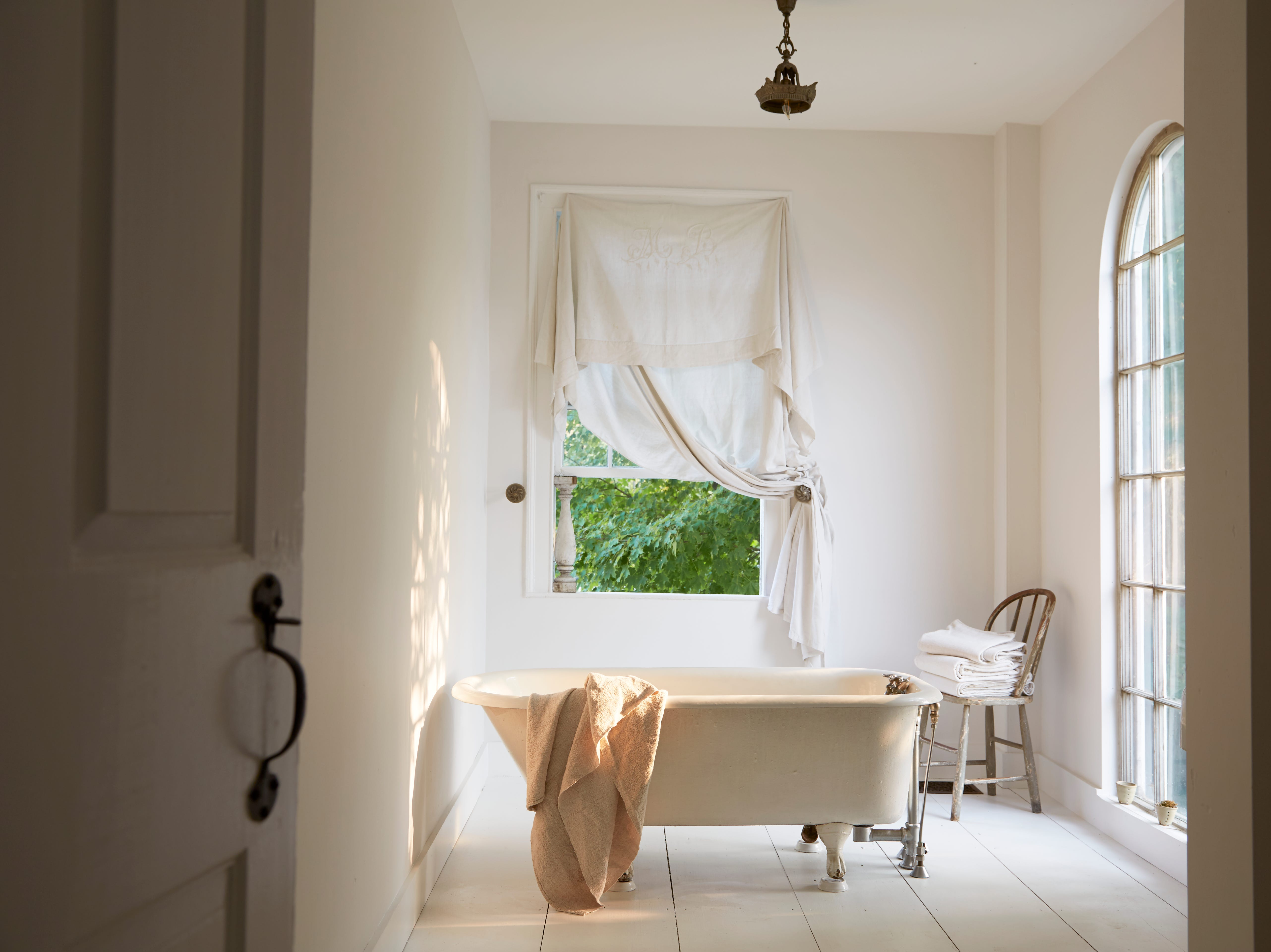 A salvaged tub in Vermont faces a west-facing arched window with a gorgeous view of the mountains.
