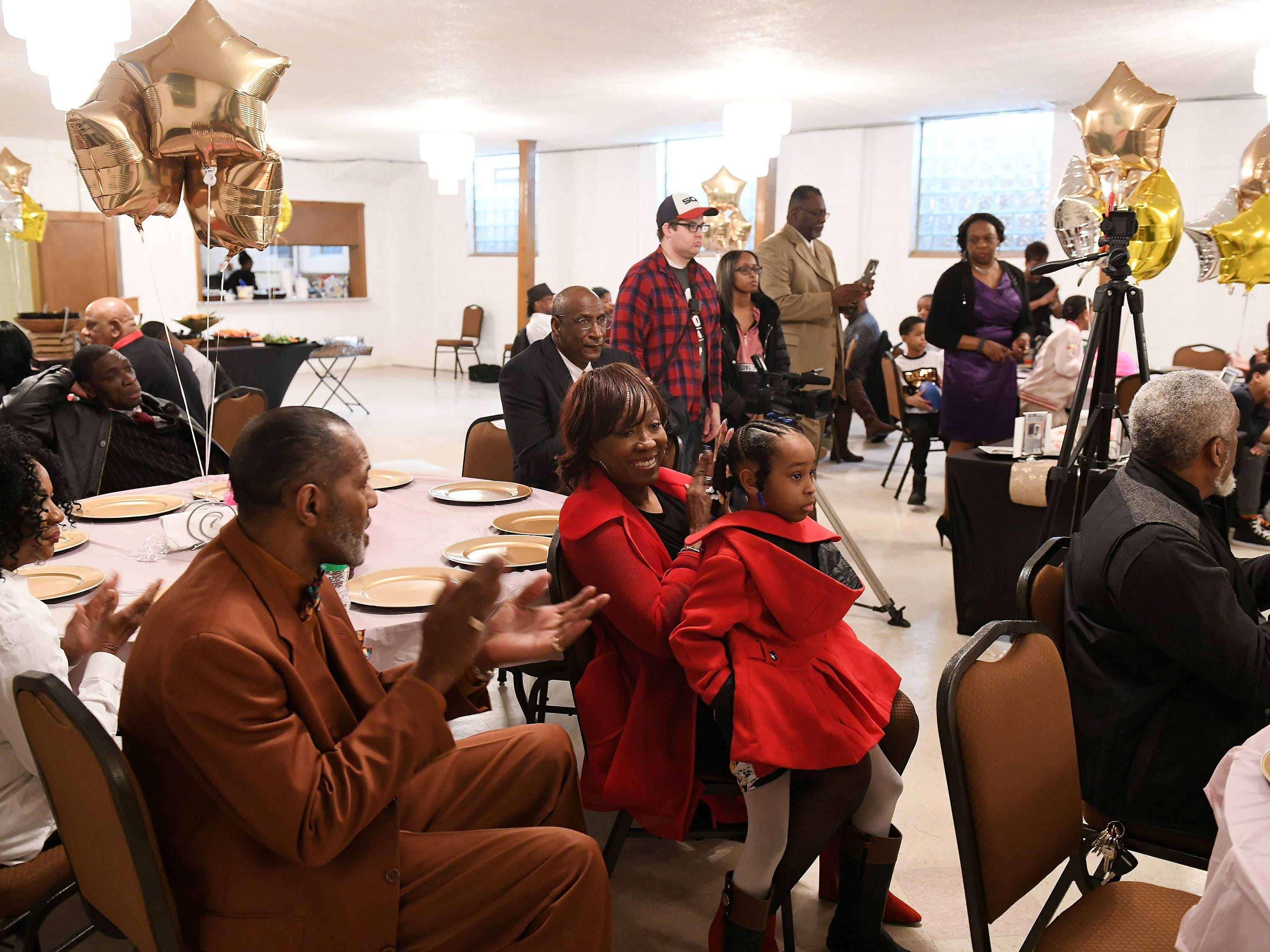 Attendees including, Don J. Griffin II, left,  and Evelyn Williams with her granddaughter, Kimiya Williams, applaud at the birthday celebration for Lois Holden.