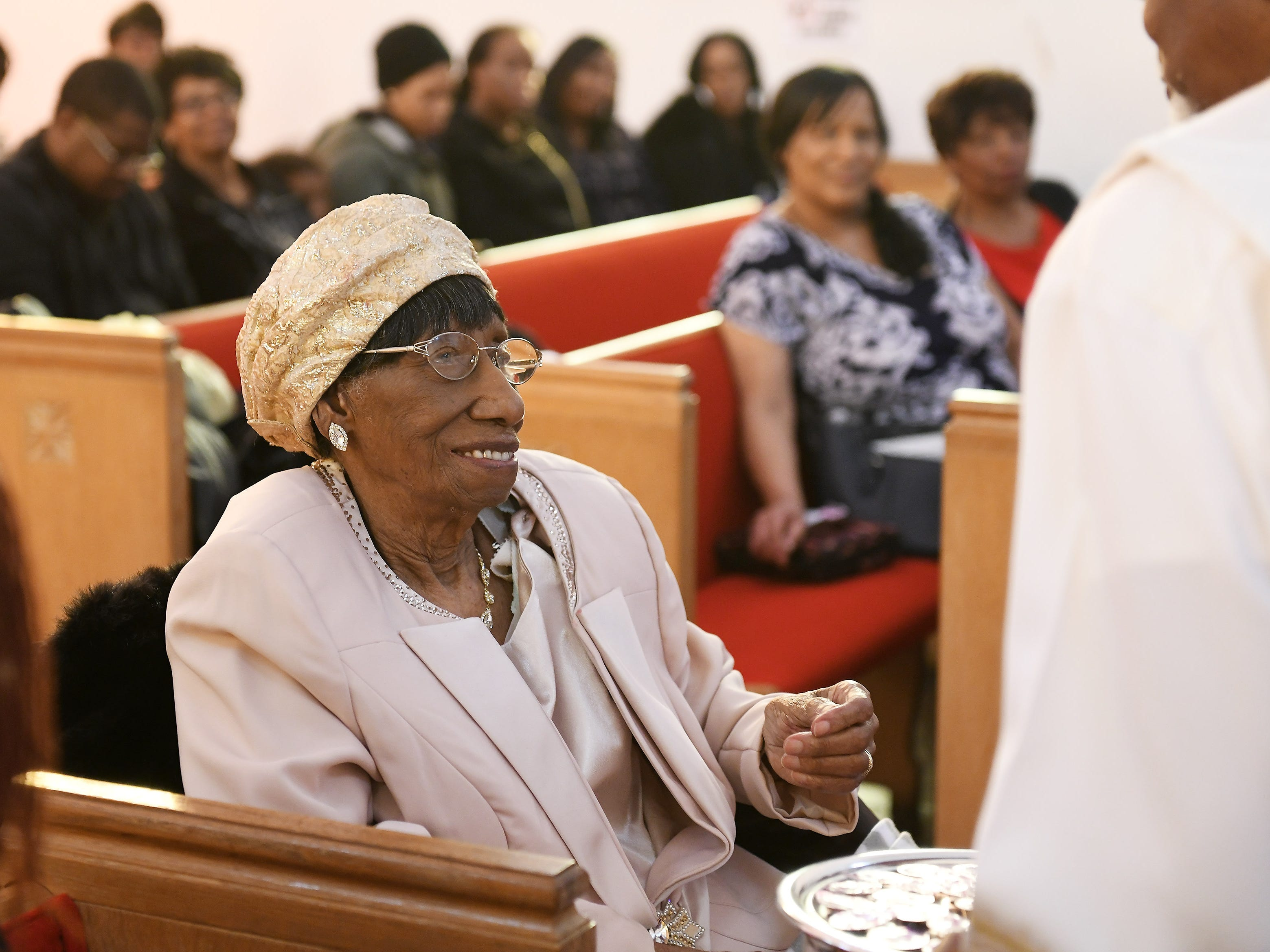 """The Rev. Earnest O. King Sr. presents """"Mother"""" Lois Holden, 109, with communion."""