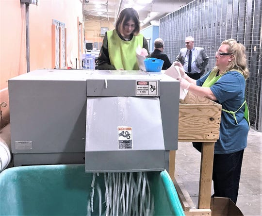 Southern Tier Industries job coach Aviva Tappan, right, hands sensitive documents to Arc of Chemung client Katie Ellis, who feeds them into a paper shredder at The Arc's Elmira headquarters.