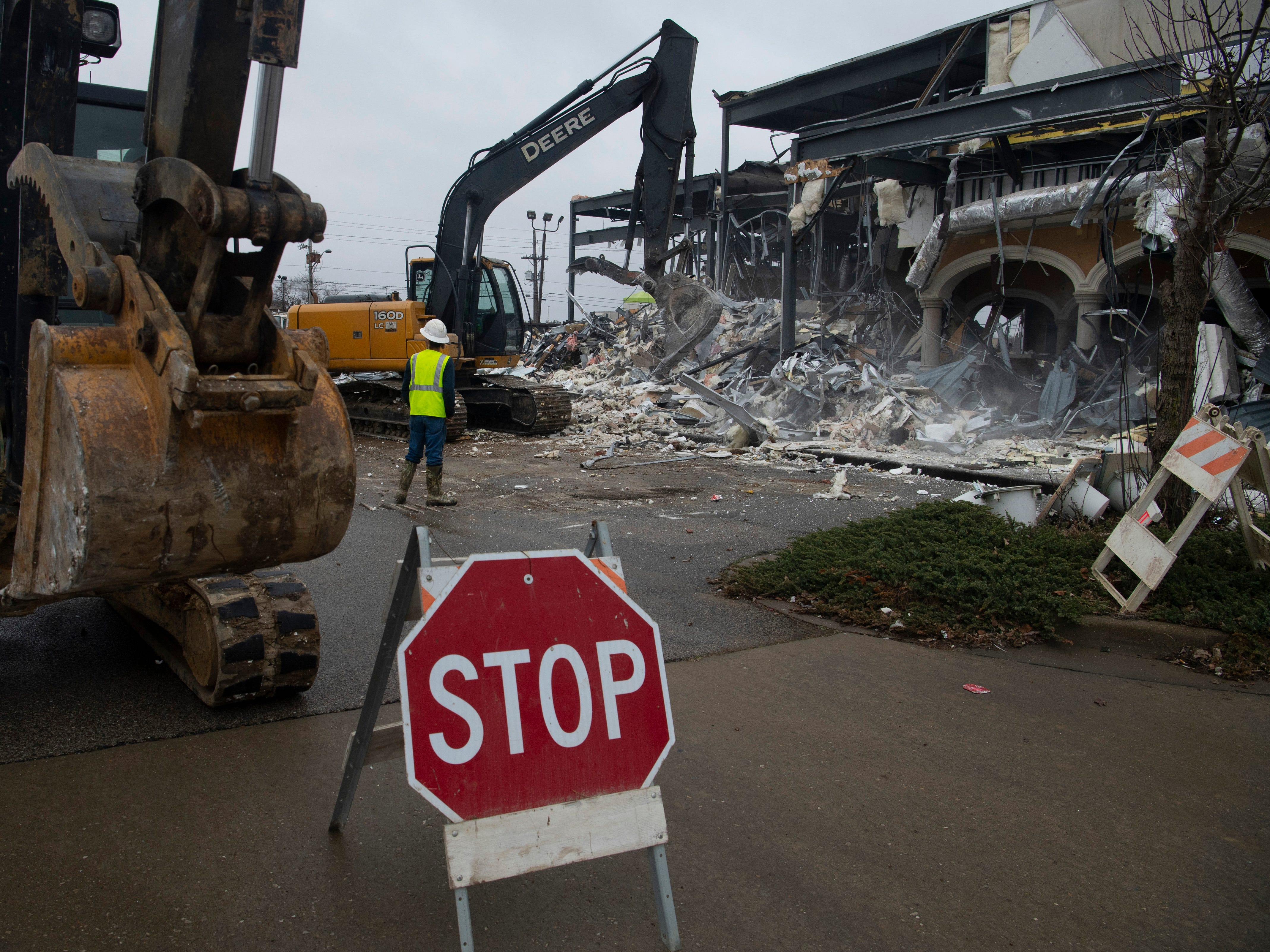 Lance Hollum with Stemaly Excavations keep the area clear as excavator operator John Hay continues the demolition of the old Nieto's Mexican Express at 1000 N. Green River Road Monday afternoon. The demolition project will make way for a new restaurant, BJ's Restaurant & Brewhouse, which will open sometime this year.