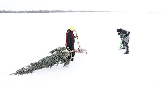 Mitch White and Scott Blanck of Van Dyne erect old pine trees Friday, Feb. 1, 2019 along an ice road the Friendship Fishing Club maintains on Lake Winnebago during sturgeon spearing season. The trees allow the road to be more visible.