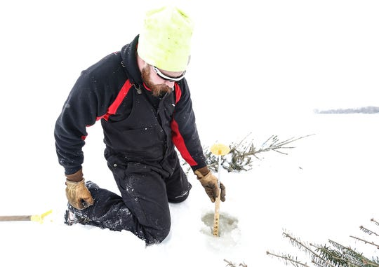 Mitch White of Van Dyne measures the thickness of the ice Friday, Feb. 1, 2019, along an ice road. Discarded pine trees are then placed in the hole to allow the road to be more visible.