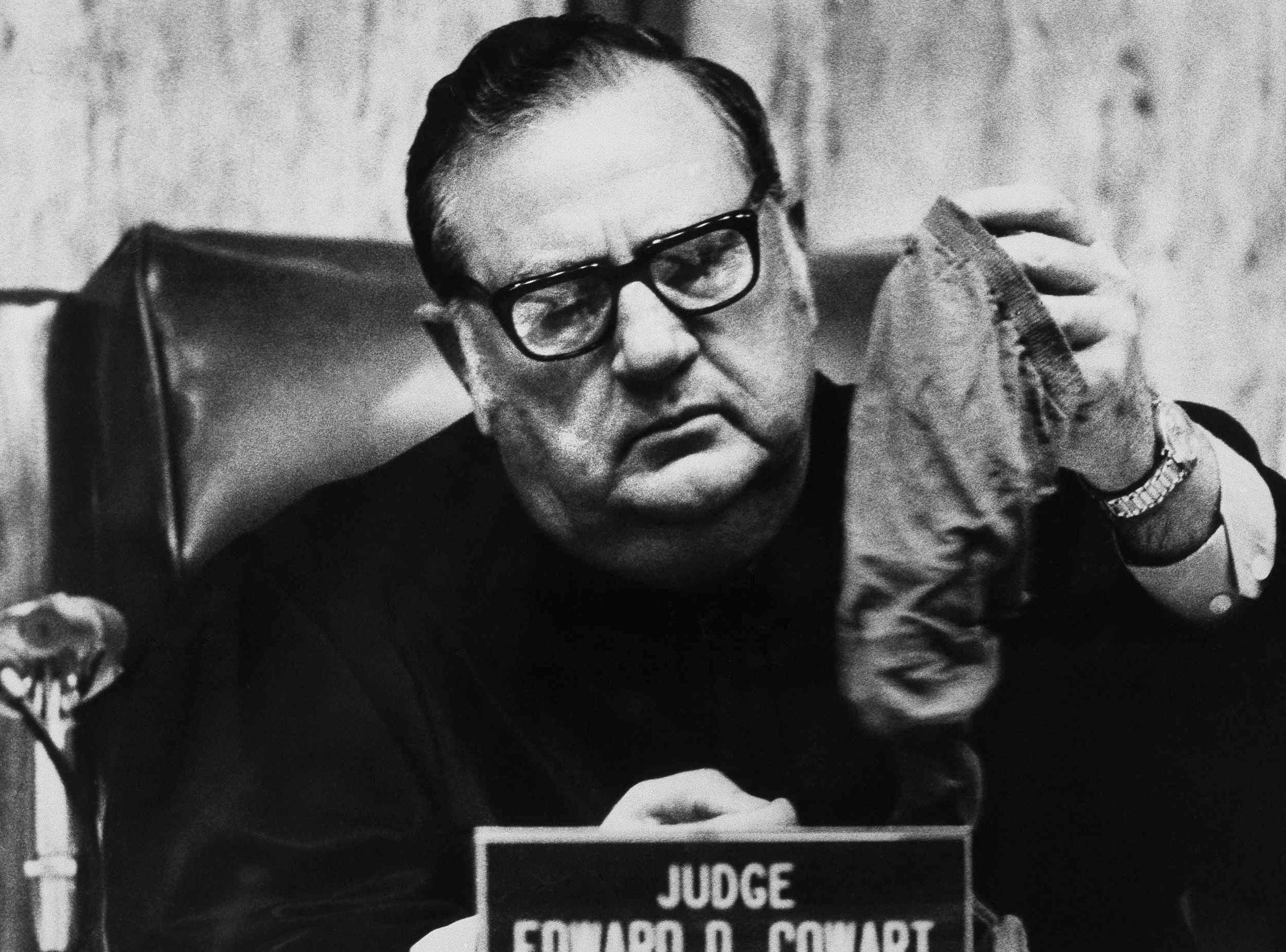 Trial Judge Edward Cowart eyes a pair of pantyhose, July 13, 1979, that the Salt Lake City police took from Theodore Bundy's automobile upon his arrest there in 1975.