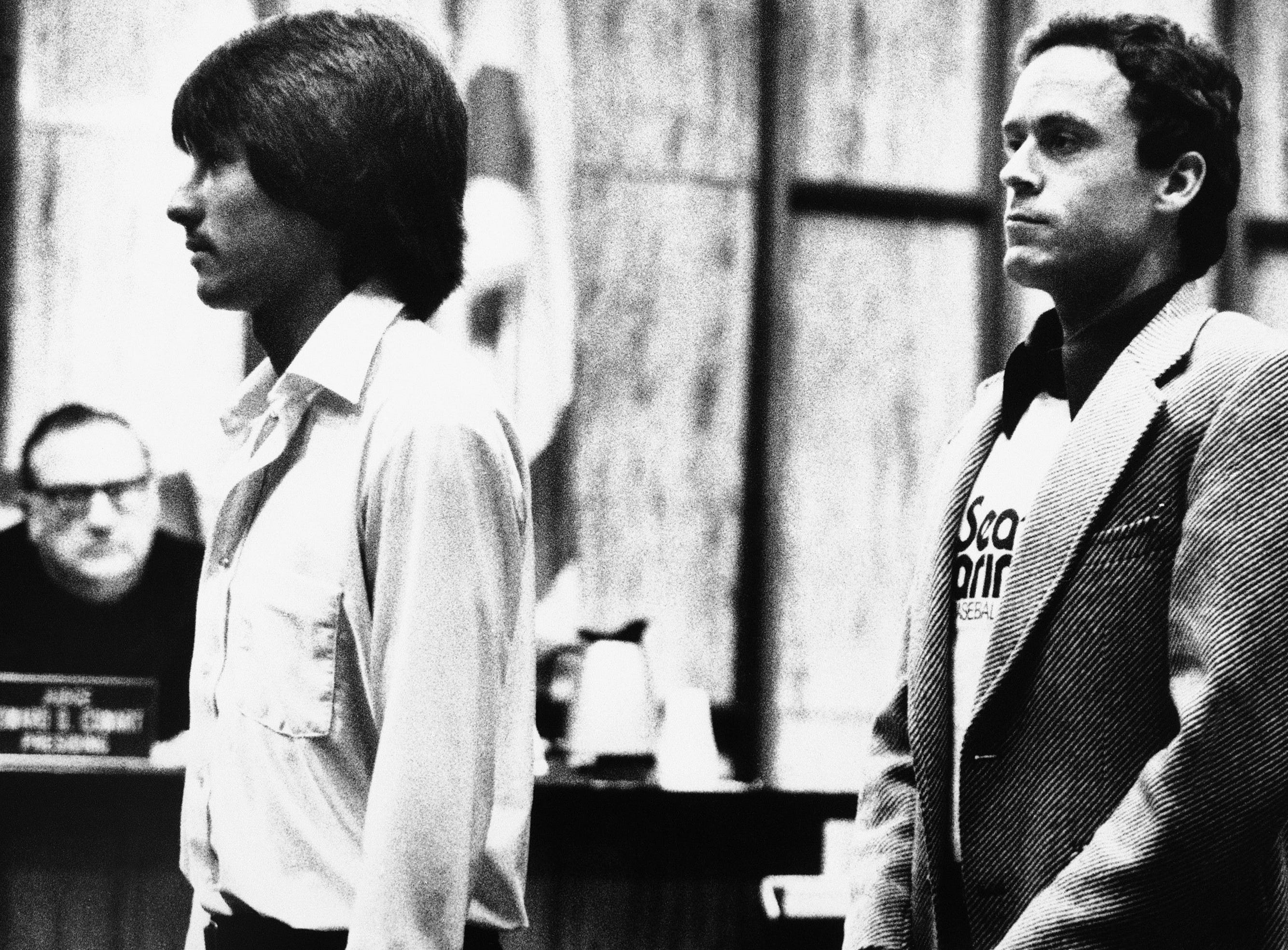 Accused murderer Theodore Bundy, right, and former Chi Omega Sorority houseboy Ronnie Eng, left, stand profile-to-profile for Bundy's defense team and trial Judge Edward Cowart, far left, in the Miami Courtroom where Bundy is on trial for the murders of two Chi Omega sorority sisters, Monday, July 5, 1979, Miami, Fla. Bundy's defense team tried to suggest that someone other than Bundy, possibly Eng, was the man seen leaving the sorority house the night of the murders.