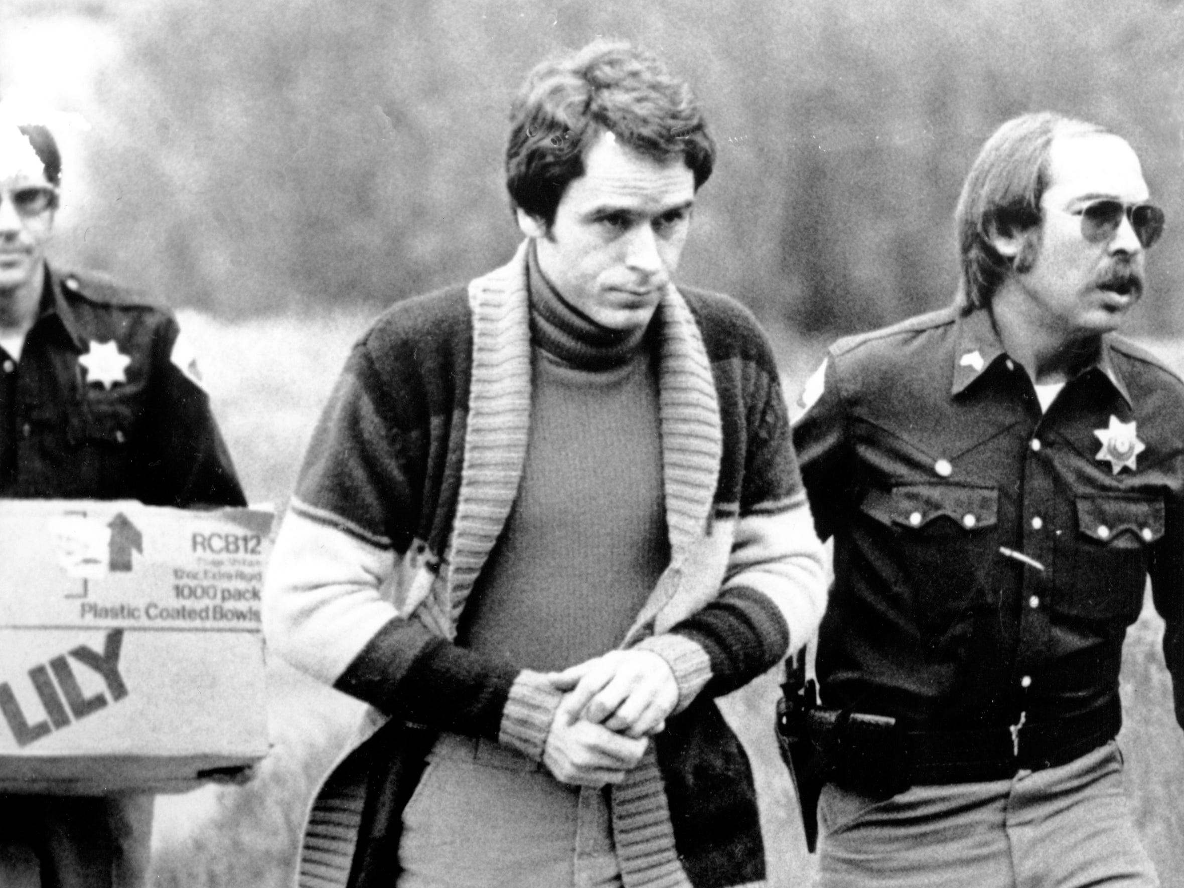 Convicted kidnapper Theodore Bundy is led into the Pitkin County courthouse by Deputy Peter Murphy, left, and Rick Kralicek for a hearing in Aspen, Colo., on June 8, 1977.  Bundy, who was being charged for murder, jumped out of a second-story window during a court recess.