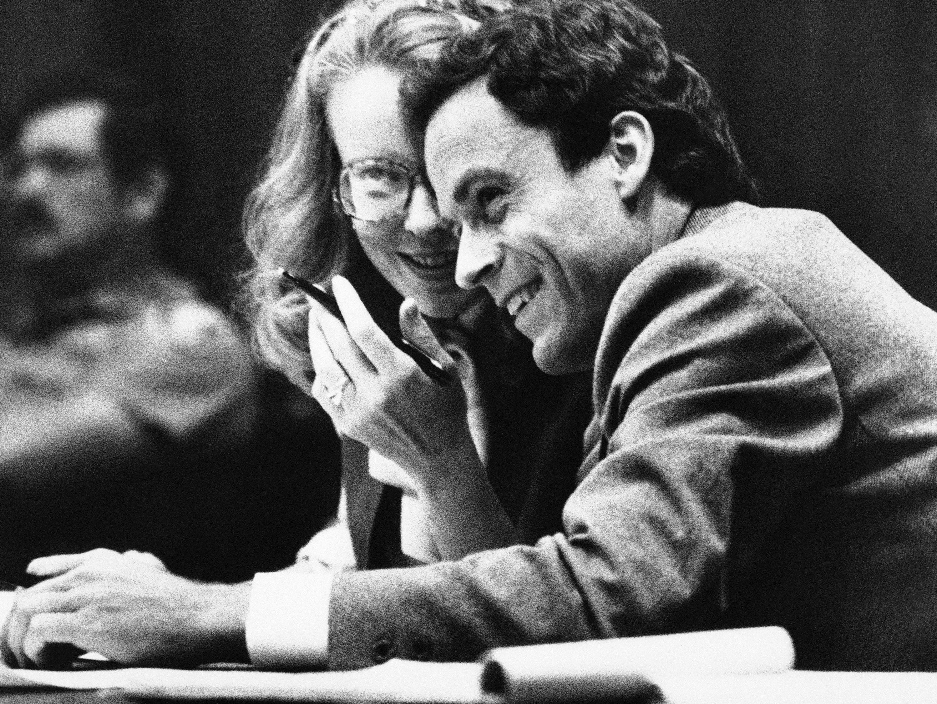Theodore Bundy, right, smiles as he huddles with Margaret Good, a member of his defense team, during the jury selection portion of Bundy's murder trial, July 6, 1979, Miami, Fla. Bundy is accused of murdering two Florida State Univ. co-eds.