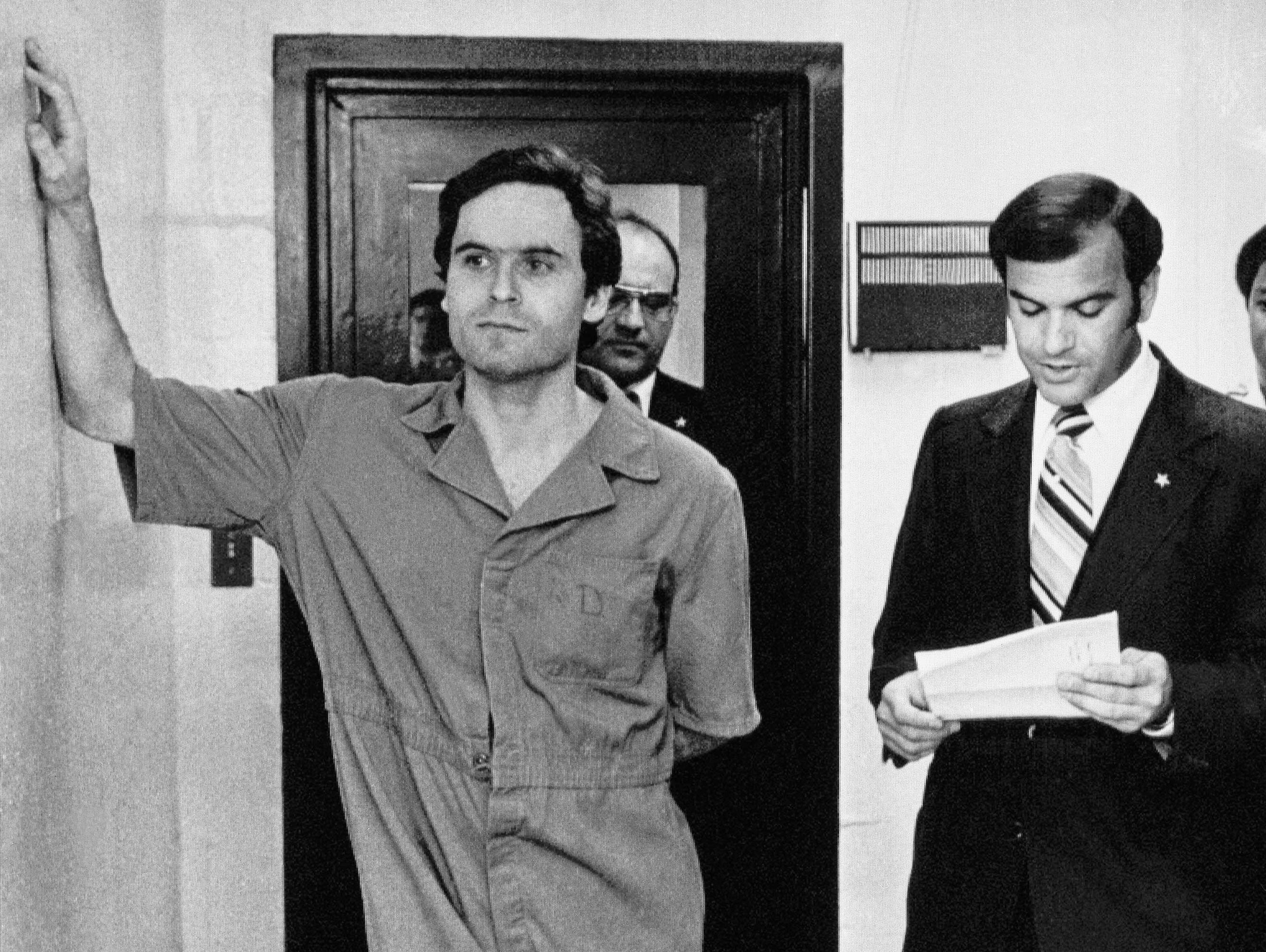 Theodore Bundy makes himself comfortable as Sheriff Ken Katsaris reads the indictment handed down by the Leon County Grand Jury, July 27, 1978 in Tallahassee, Fla.  Bundy was indicted on two counts of first degree murder; three counts of attempted murder and two counts of burglary.