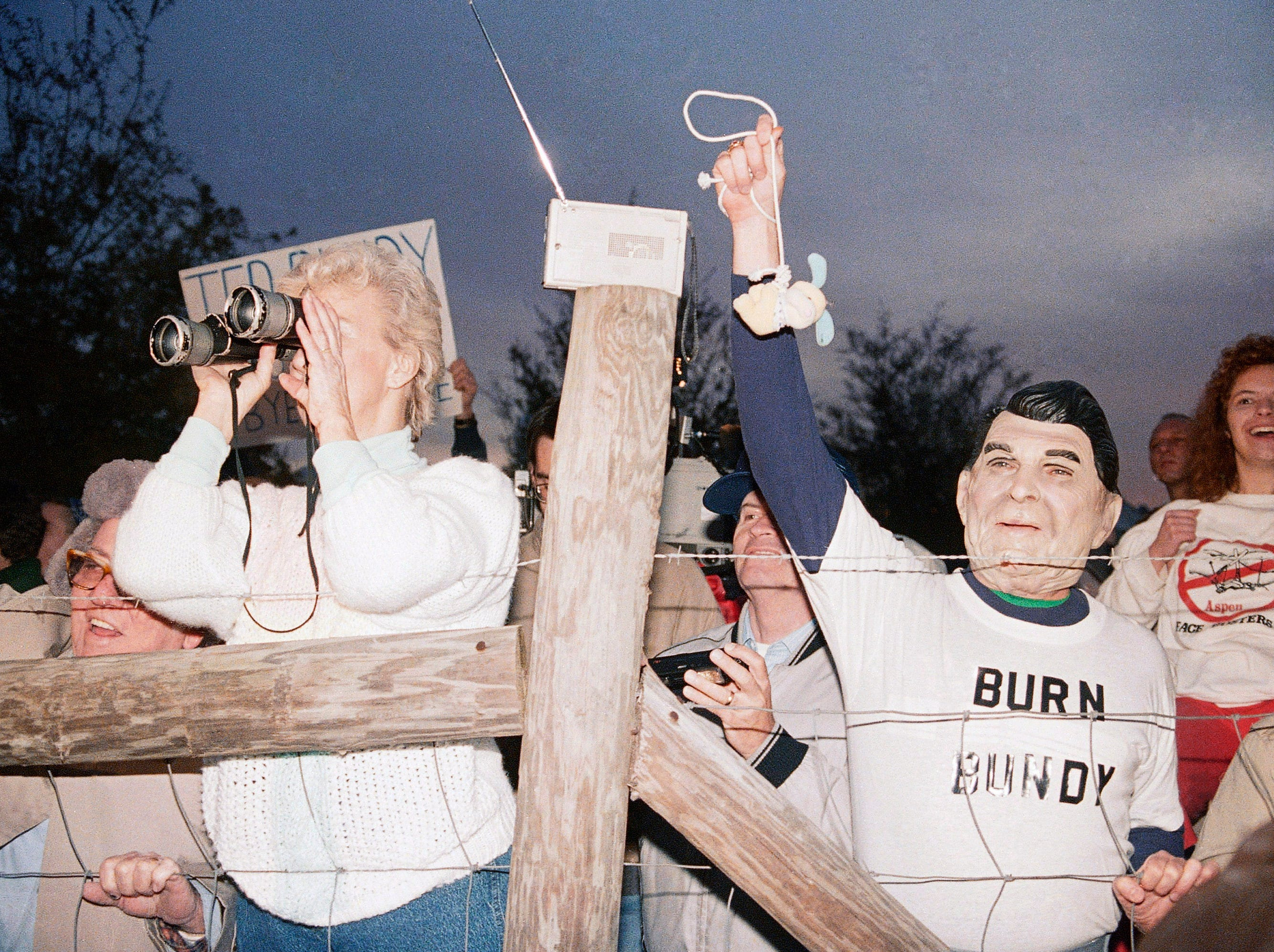 A toy bunny is hung in effigy by Jerry Jackson of Atlanta Ga., wearing a Ronald Reagan mask, and the pro-death penalty crowd rejoices after the Theodore Bundy execution, Jan. 24, 1989 at sunrise in Starke, Fla.