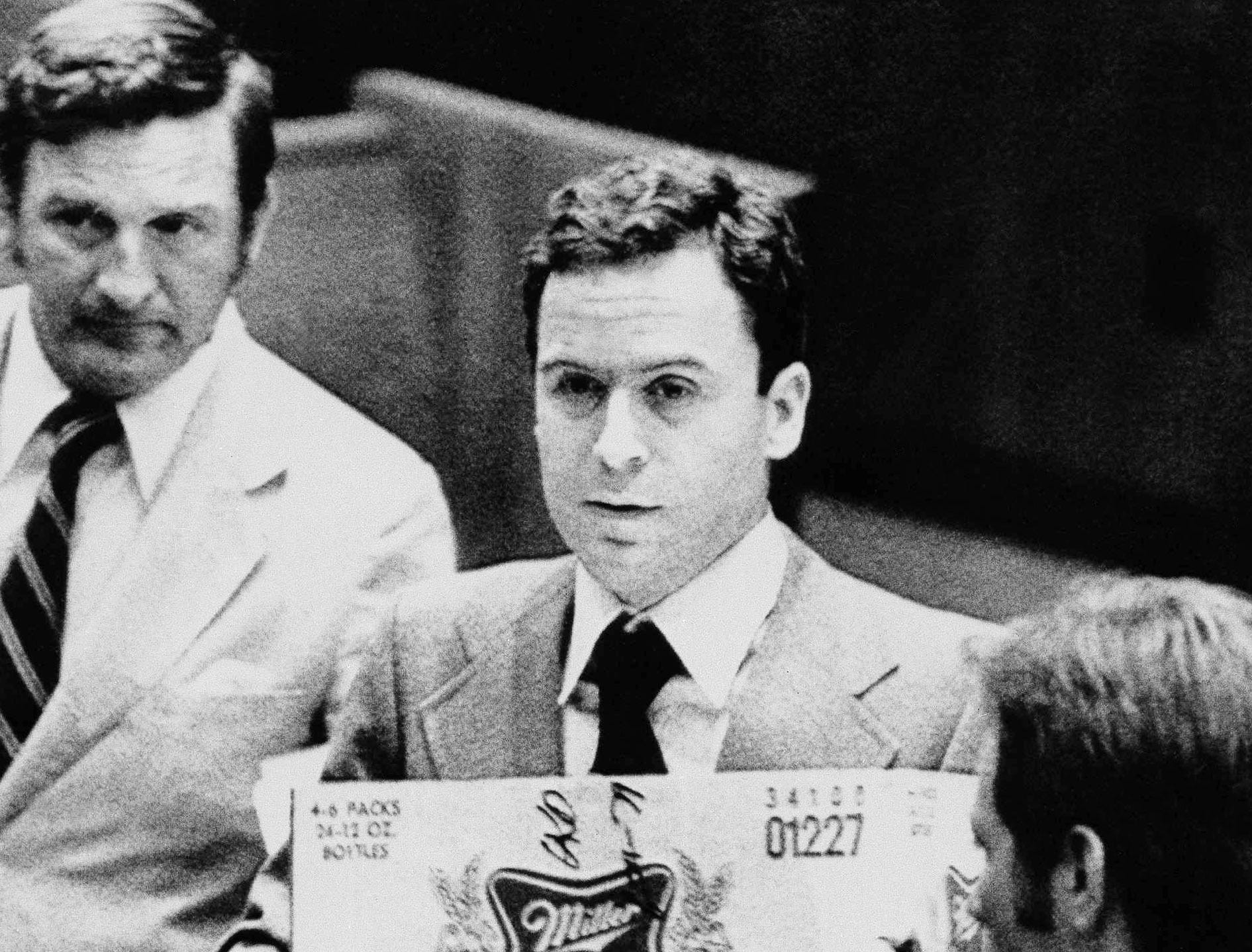 "Theodore Bundy, convicted last month on charges of slaying two Florida State University coeds, leaves court, Aug. 27, 1979, in Tallahassee with his ""beer box briefcase"" after being denied a new trial."
