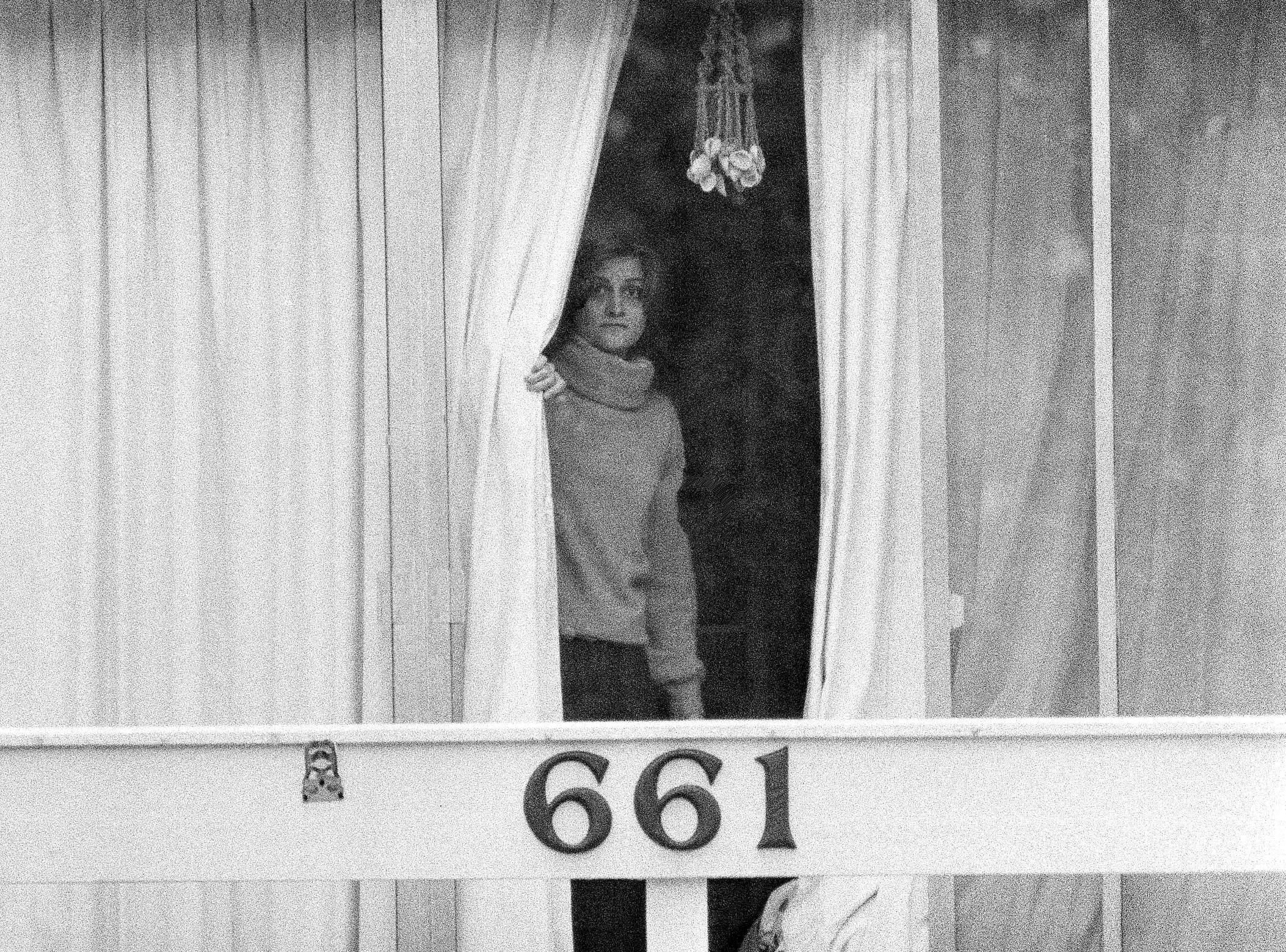 An unidentified woman peers through drapes on the 2nd story balcony of the Chi Omega sorority house at Florida State University in Tallahassee, Fla., Jan. 15, 1978. Two sorority sisters, Margaret Bowman and Lisa Levy, were brutally beaten to death with the assailant leaving 3 others injured early Sunday morning.
