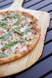 Blaze Pizza makes its White Top pizza with white cream sauce, mozzarella, applewood bacon, chopped garlic, oregano and arugula.