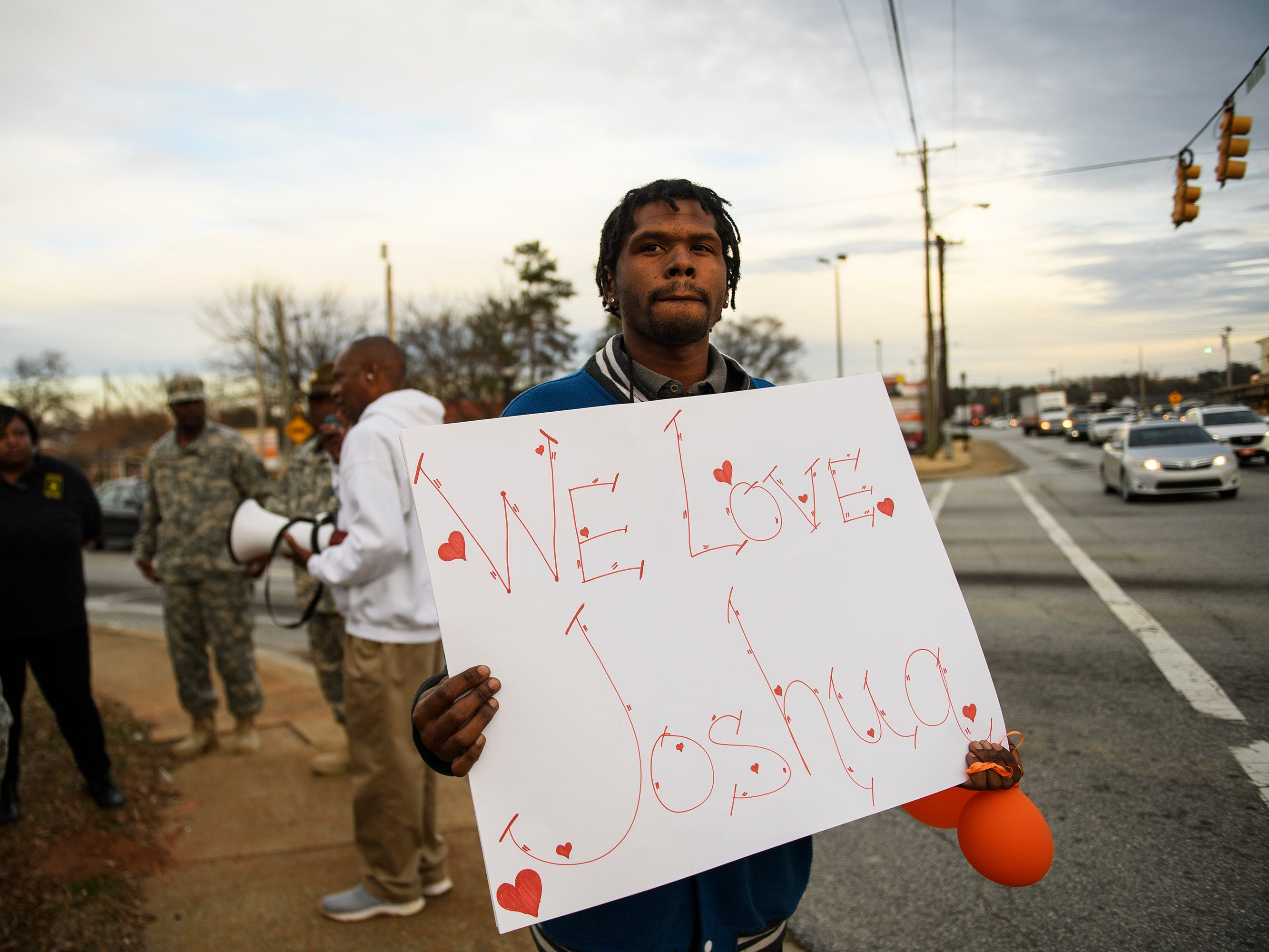 Thomas Young holds a sign during a balloon release in honor of Joshua Meeks on East Butler Road in Mauldin on Feb. 4, 2019.