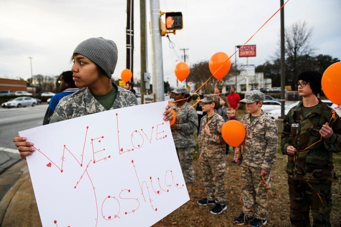 Maya Scott holds a sign during a balloon release in honor of Mauldin High School student Joshua Meeks on East Butler Road on Feb. 4, 2019.