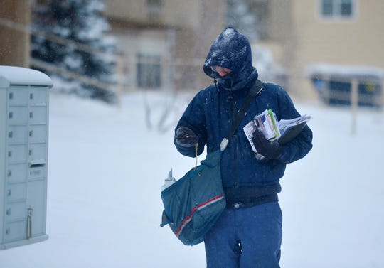 Mail carrier Tony Juntunen walks his route near the Market Place on Monday morning.  Juntunen says that walking actually helps him stay a little warmer on cold days than driving in his delivery truck.