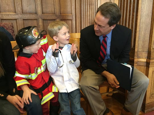 Gov. Steve Bullock chats Monday with Hudson and Mason, center, Van Nice prior to a news conference on school funding.