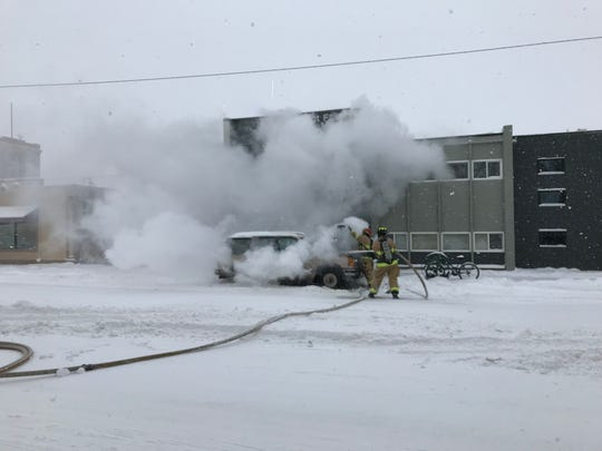 Firefighters douse a Chevy Blazer that caught fire Monday morning in front of the Great Falls Rescue Mission Womens Shelter.