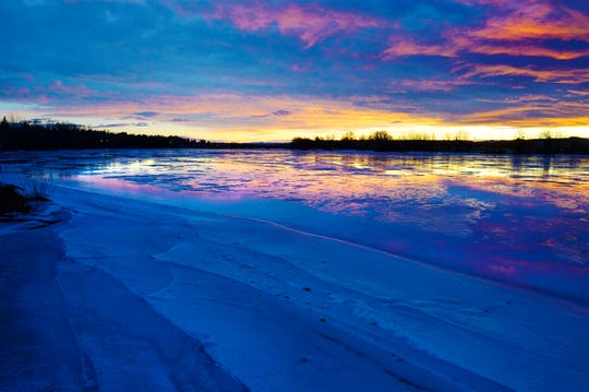 A colorful sunset reflects off the ice melt at Broadwater Bay, Jan 31, 2019.