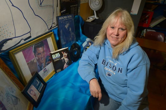 Julie Anderson poses with some of her mother's Elvis Presley memorabilia. Anderson's mother passed away about a year ago and so the family has decided to sell some of the collection.