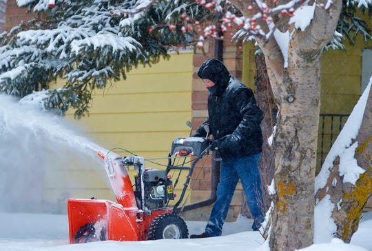 Lee Scott clears snow for a neighbor on Monday morning.