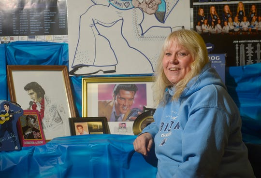 Julie Anderson poses with some of her mother's Elvis Presley memorabilia.  Anderson's mother passed away last year and so the family has decided to sell some of the collection.