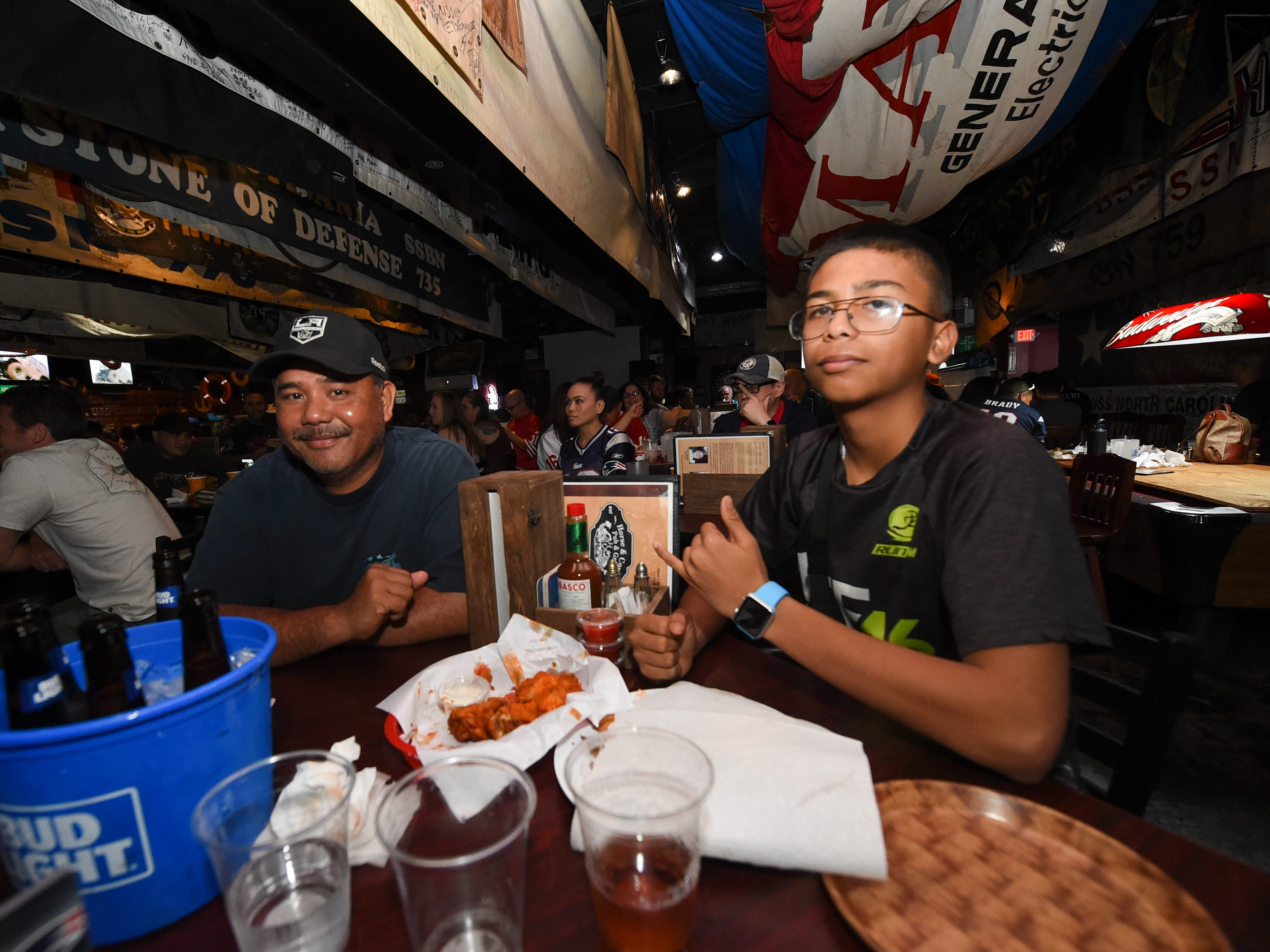 G'vonni Perez, right, watches Superbowl 53 with his uncle Rudy Chargualaf during a party at Horse and Cow in Tamuning, Feb. 4, 2019.