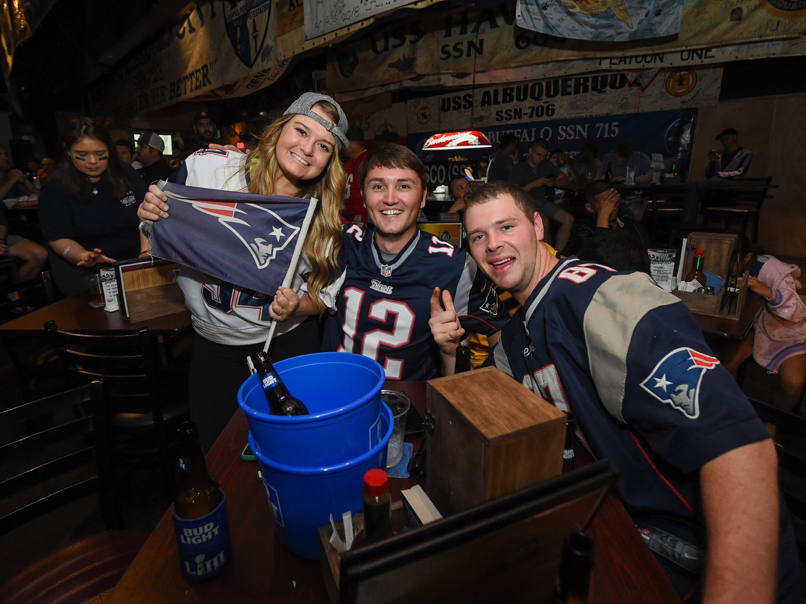 New England Patriots fans Jeff Kroeber, right, Mike Bonafilia, and Jackie Walsh sport their team's jerseys during a Horse and Cow Superbowl 53 party in Tamuning, Feb. 4, 2019.