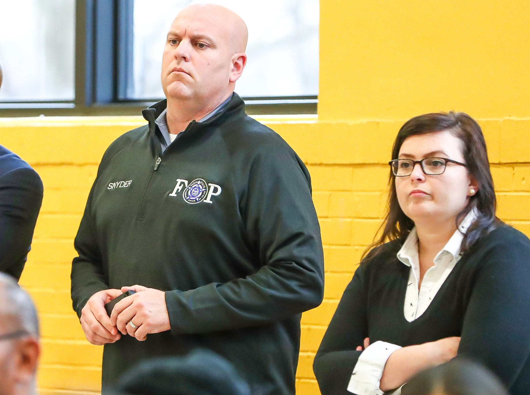 Rick Snyder (left), president of the Indianapolis Fraternal Order of Police, watches as a new pilot program to test body worn cameras is announced during a press conference at the Edna Martin Christian Center in Indianapolis on Monday, Feb. 4, 2019.