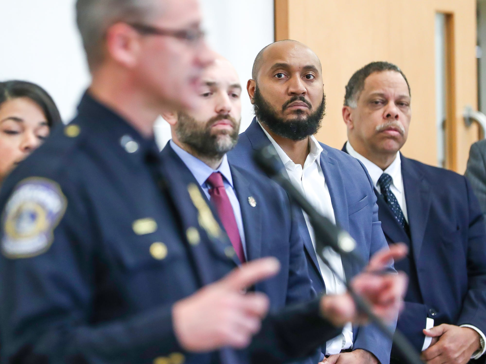 David Hampton (middle right), deputy mayor of neighborhood engagement in Indianapolis, listens as Indianapolis Metropolitan Police Department Chief Bryan Roach speaks about the start of a process to study body worn cameras during a press conference at the Edna Martin Christian Center in Indianapolis on Monday, Feb. 4, 2019.