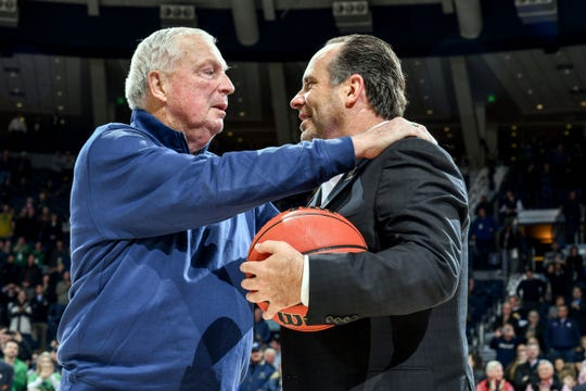 Fighting Irish coach Mike Brey is congratulated by former coach Digger Phelps after Brey passed Phelps as the program's winningest coach in program history with 394 wins.