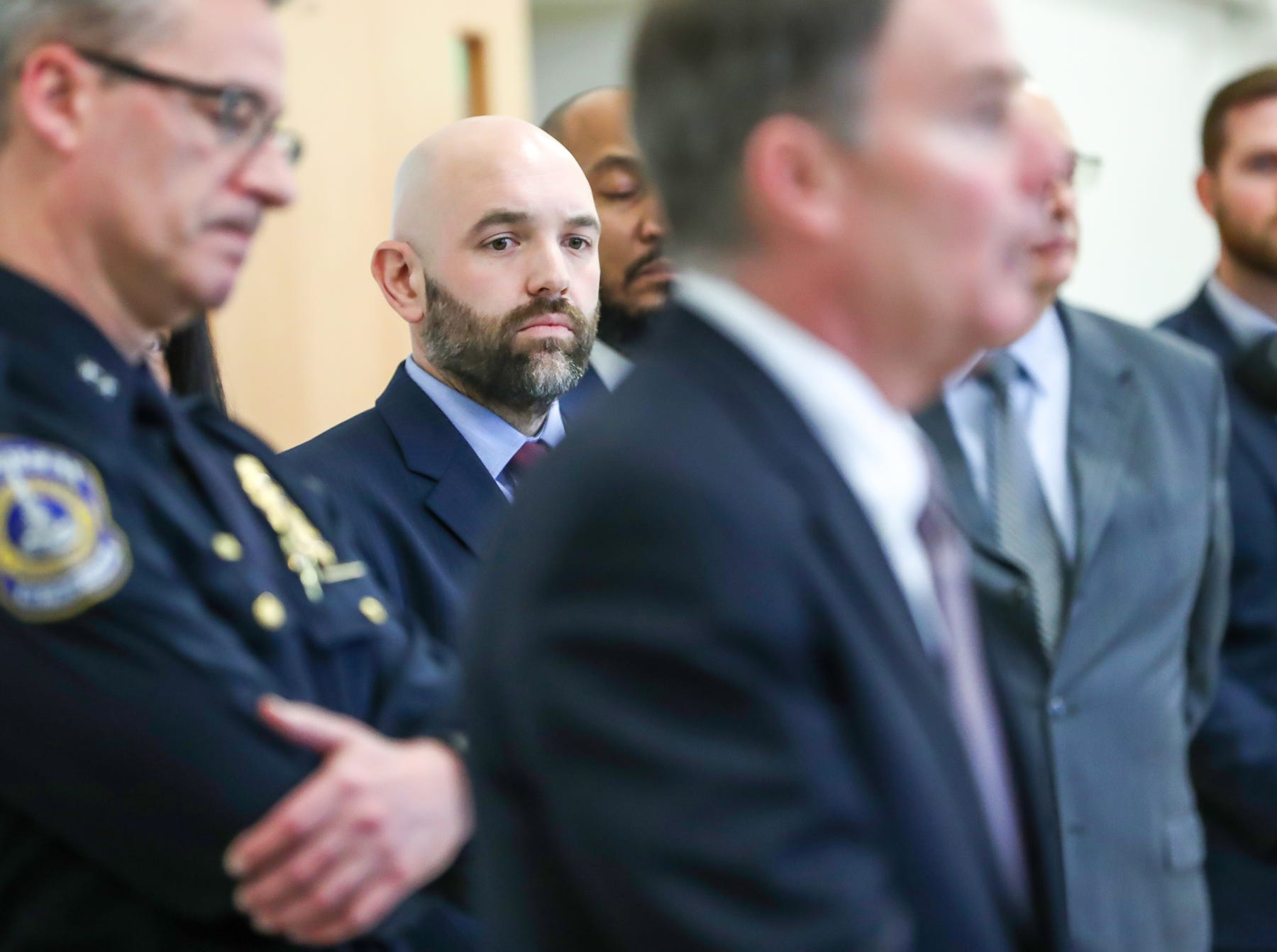 """Jeremy Carter (middle left), director of criminal justice and public safety and associate professor in the School of Public and Environmental Affairs at IUPUI, listens as Indianapolis Mayor Joe Hogsett speaks about a new program to equip IMPD officers with body worn cameras during press conference at the Edna Martin Christian Center in Indianapolis on Monday, Feb. 4, 2019. """"For year to year operation, we estimate a cost between $2 million and $3 million,"""" Hogsett said. """"Far less than earlier body cam programs would have required."""""""