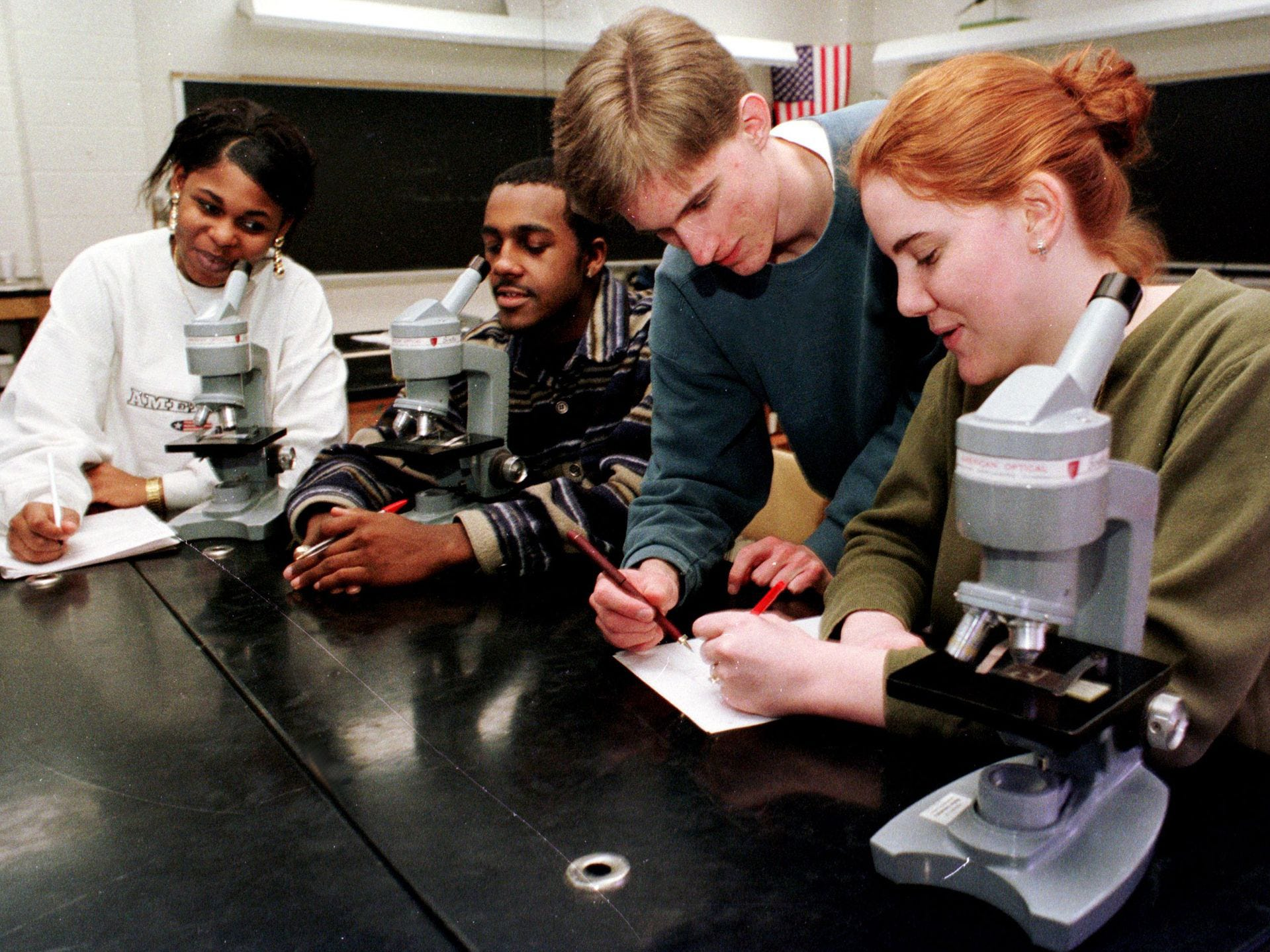 Broad Ripple students enjoy microscopes which were donated by Butler University in 1999. Butler donated 28 microscopes to Broad Ripple Ôs biology program after they replaced them with new scopes for their students. L to R: Juanita Oakley (white shirt); Columbus Kirkland (stripes); Kevin Lantry ; and Katy Vawter.