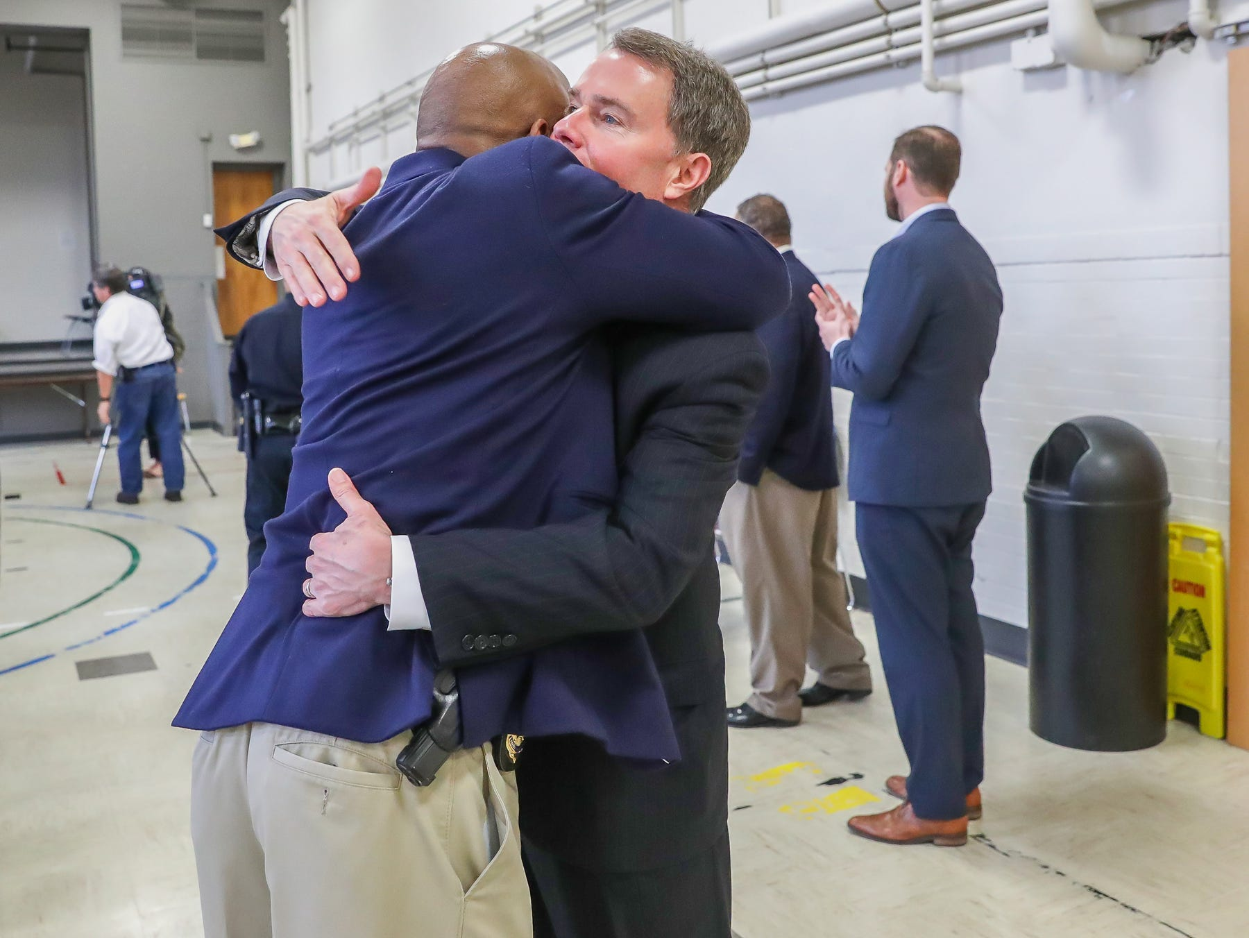 Indianapolis Mayor Joe Hogsett (right) hugs Capt. John H. Walton Jr., a 36-year IMPD veteran who was recently named director of Diversity and Inclusion, after the announcement on the start of a process to study body worn cameras on IMPD officers during a press conference at the Edna Martin Christian Center in Indianapolis on Monday, Feb. 4, 2019.