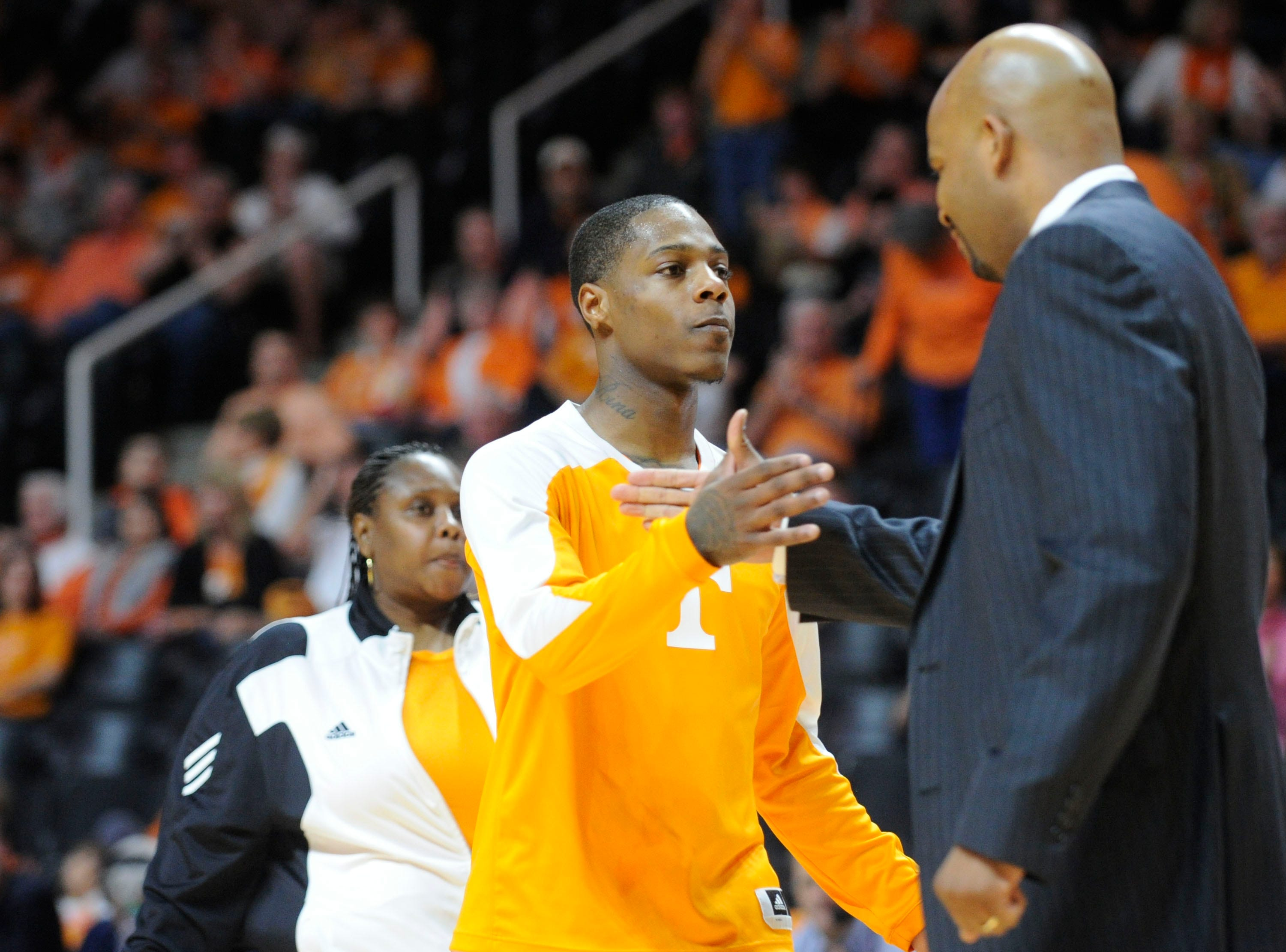 Tennessee guard Antonio Barton (2), center, shakes hands with Tennessee head coach Cuonzo Martin as he is recognized on senior day before Tennessee's game against Missouri at the Thompson-Boling Arena in Knoxville on Saturday, March 8, 2014.