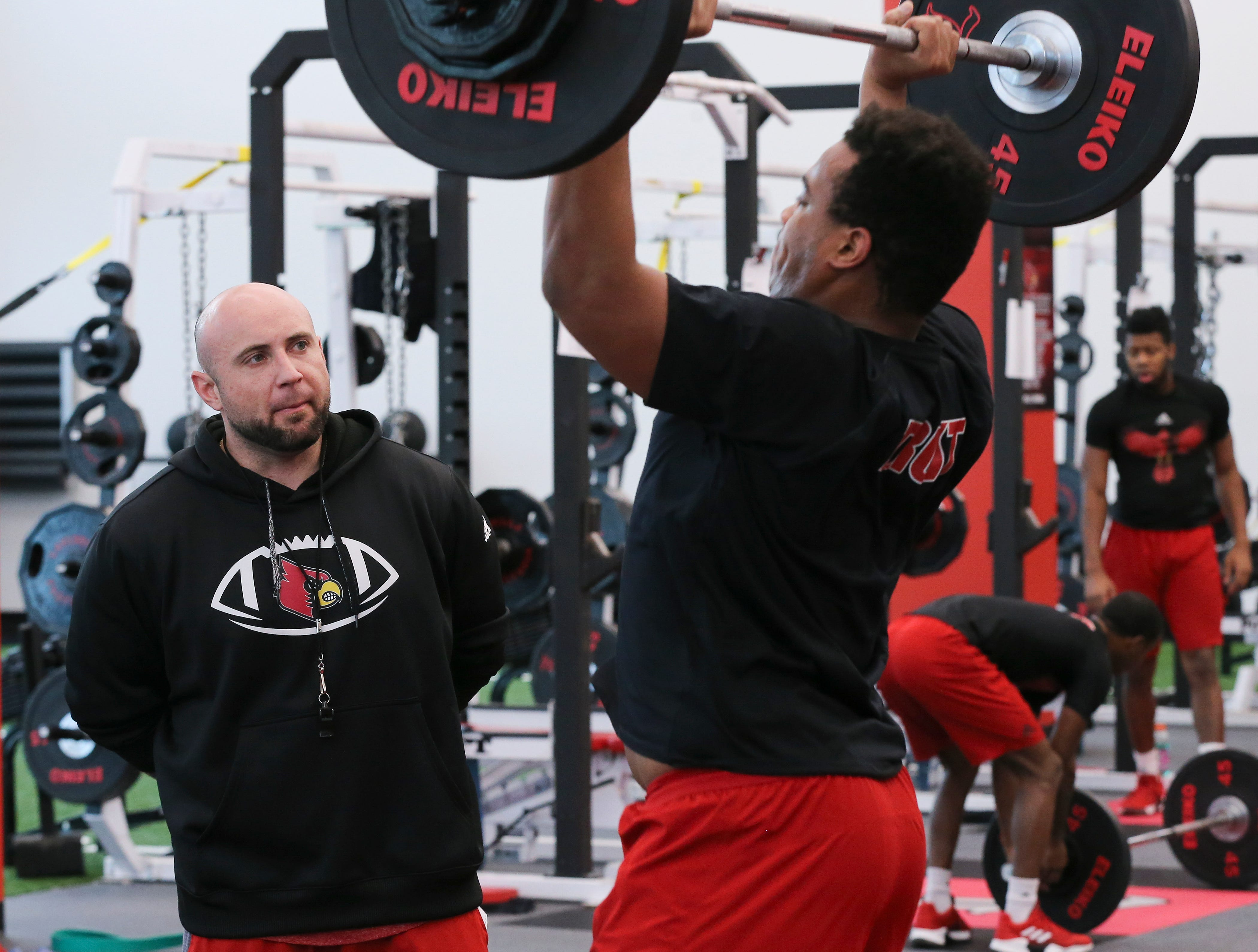 U of L strength coach Mike Sirignano, left, observes Caleb Chandler as he presesses weights during strength and conditioning at the Schnellenberger Complex.